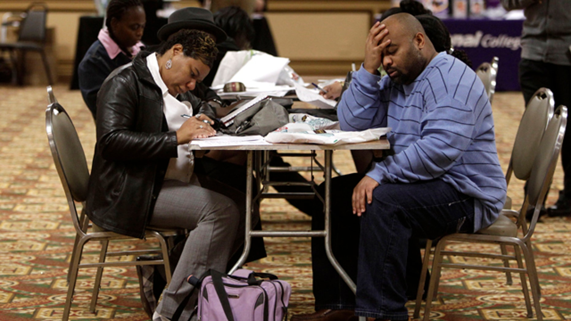 Oct. 26, 2011: Tonya Crenshaw and Kendrick Haraalson fill out applications at a job fair in Brookpark, Ohio. The number of people seeking unemployment benefits dipped slightly last week, though not by enough to suggest that hiring is picking up.