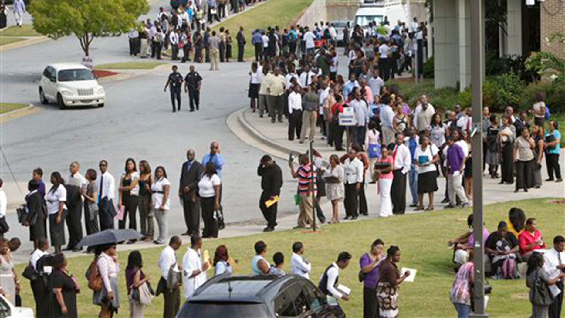 In this Aug. 18 file photo, people wait in line during a job fair in Atlanta.
