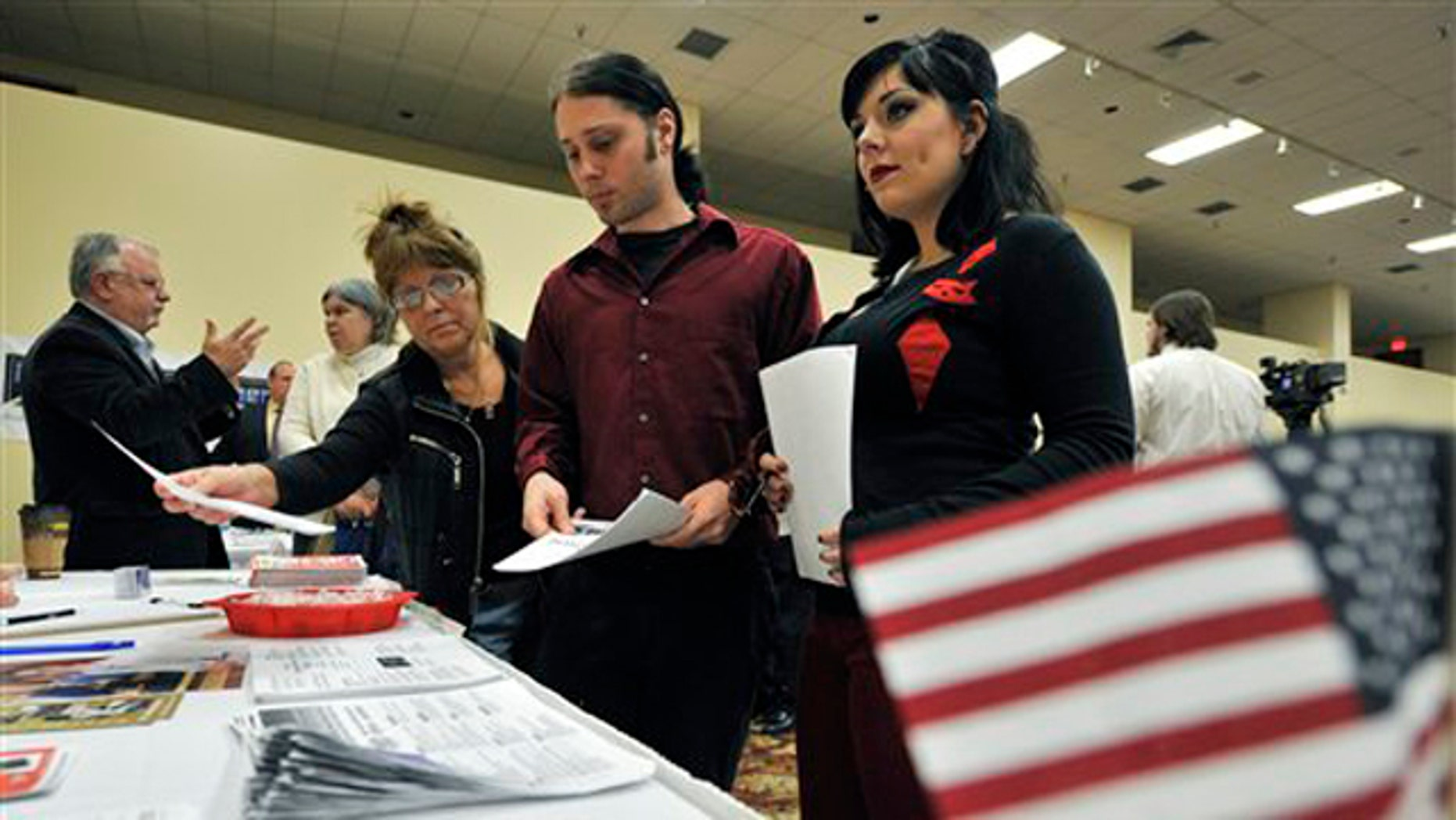 In this Oct. 5 photo, job seekers browse through information at a jobs fair in Rockford, Ill. (AP Photo)