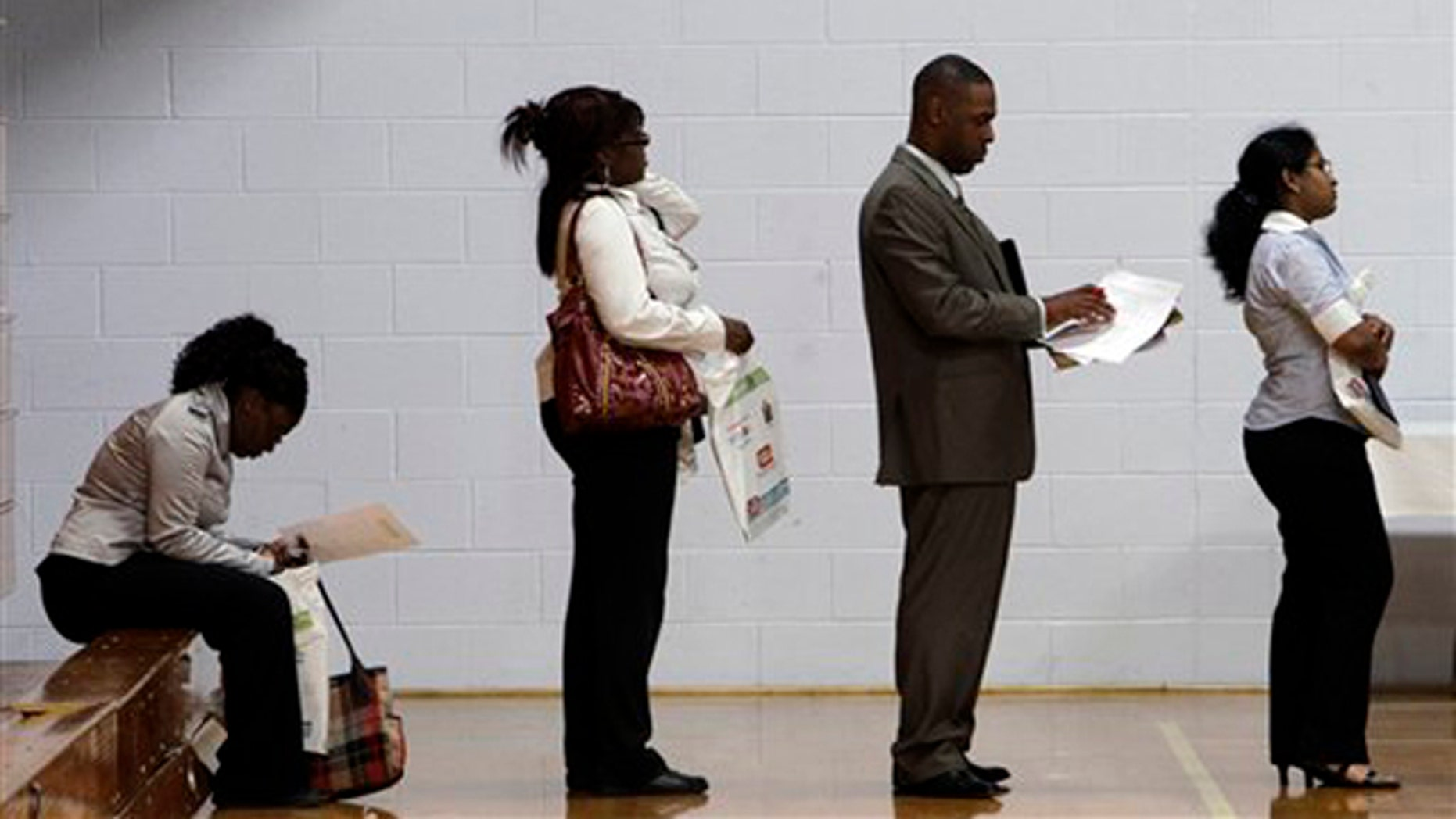 In this June 15 photo, job seekers wait in a line at a job fair in Southfield, Mich.