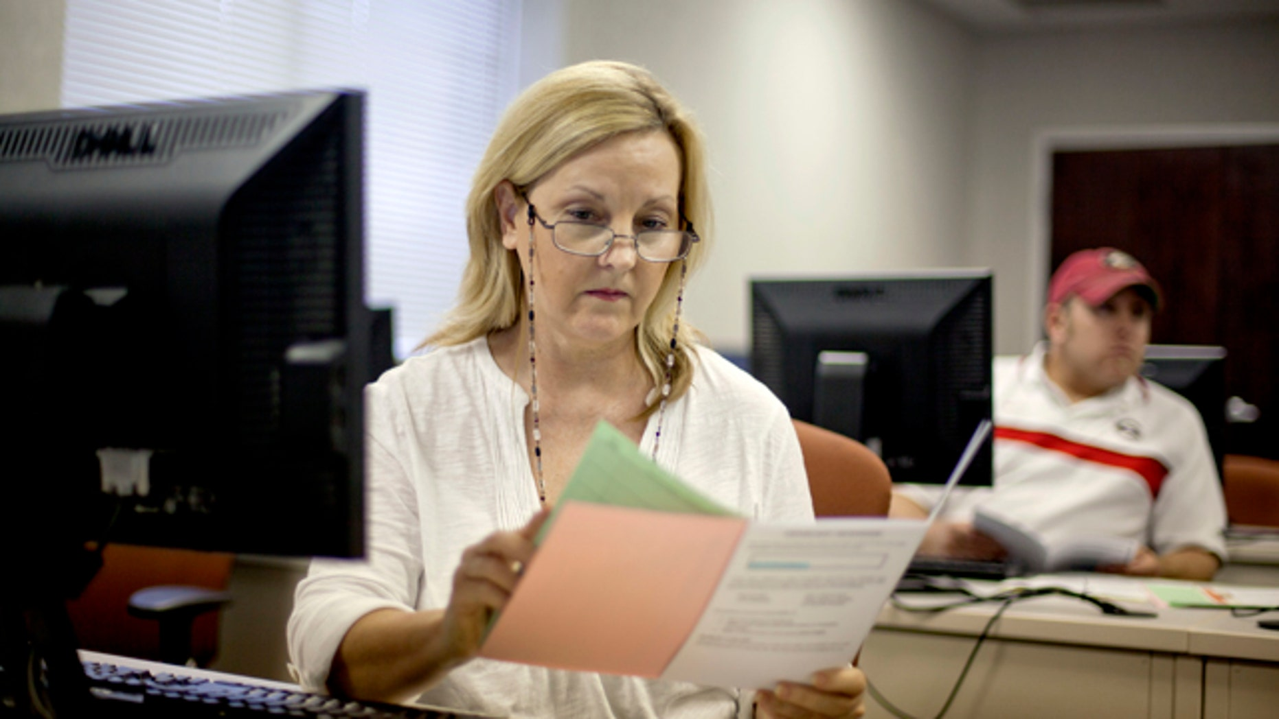 Aug. 22, 2012: Judy Smith, of Dalton, Ga., looks over paperwork as she files for unemployment for the first time since being laid off from a catering job at a convention center in Dalton, Ga. (AP)