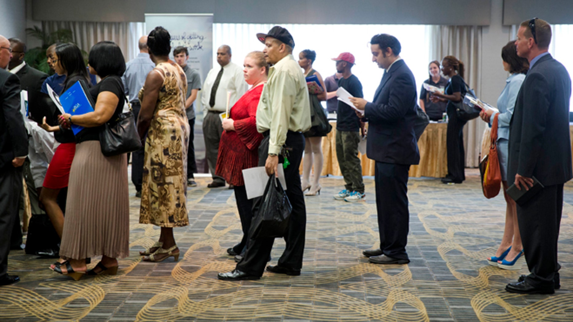 In this June 23, 2014 photo, people wait in line to meet with recruiters during a job fair in Philadelphia.