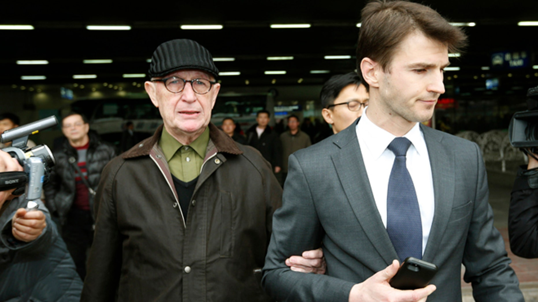 In this March 3, 2014 file photo, Australian missionary John Short, left, walks out from the airport terminal as he arrives at Beijing International Airport in Beijing, China. Short who was detained in North Korea for trying to spread Christianity said Wednesday, March 5, he was interrogated for four hours a day and kept under 24-hour guard during his grueling 13-day investigation.
