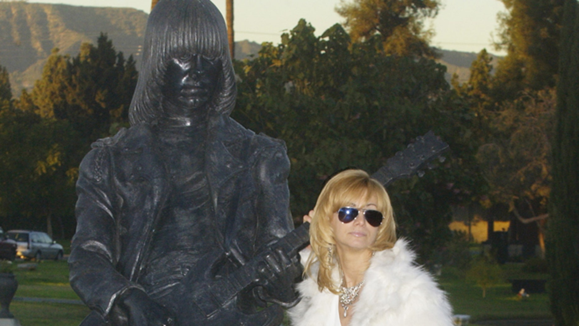 Linda Ramone, widow of Johnny Ramone poses next to a statue of his likeness in Los Angeles.