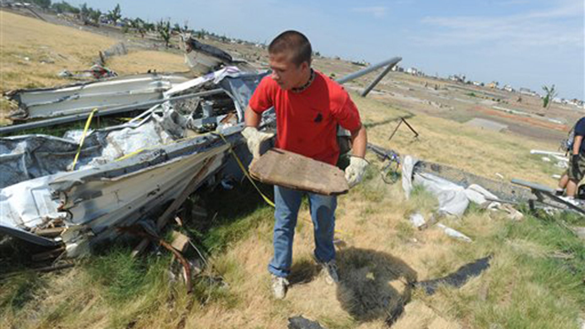 A boyscout volunteers to clean up debris from the tornado on a high school sports field.