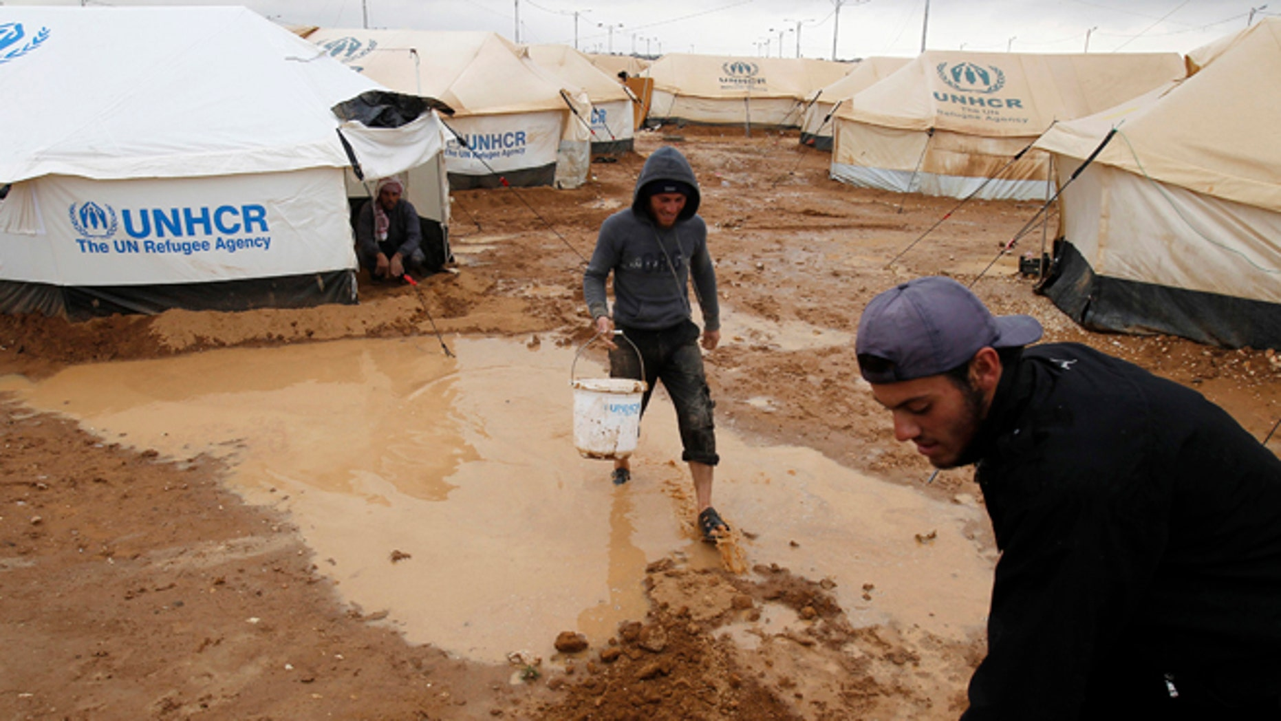 Jan. 8, 2013: Syrian refugees work to clear water collected outside their tents after heavy rain at the Al-Zaatari refugee camp in the Jordanian city of Mafraq, near the border with Syria.