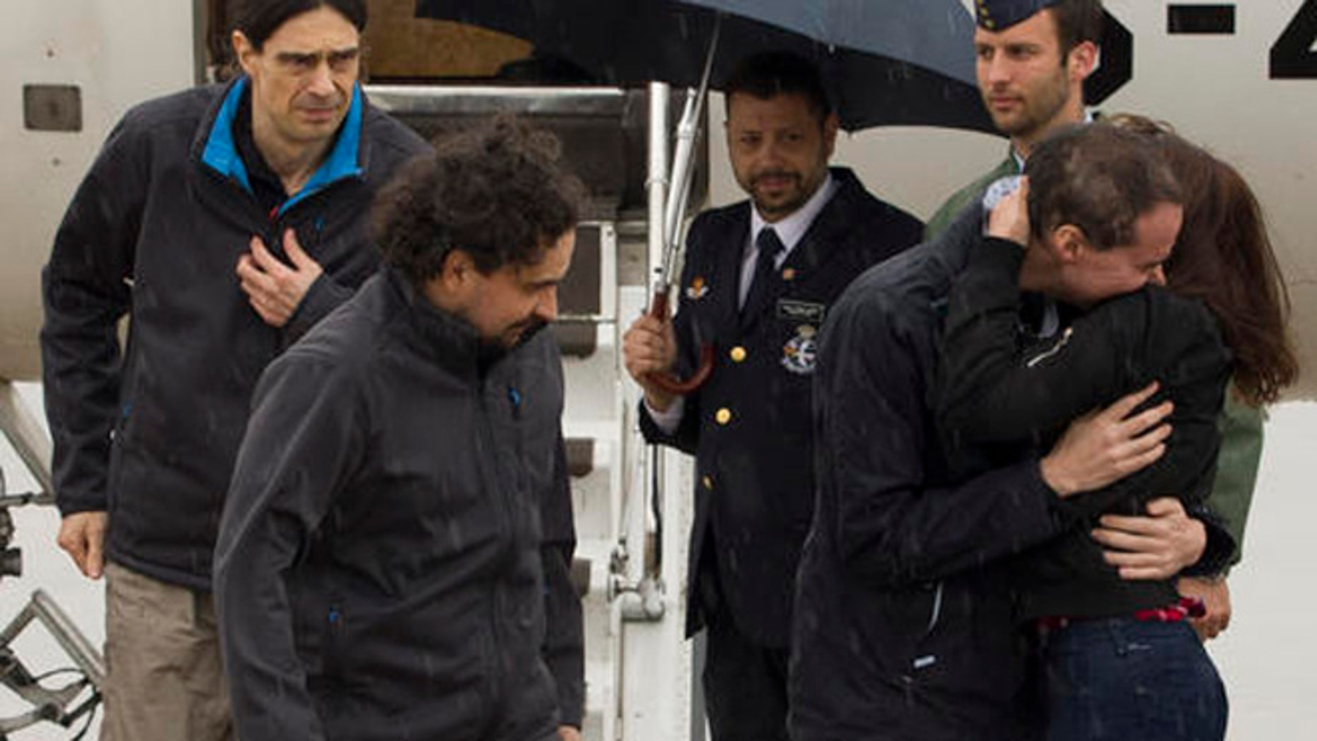 The three freed Spanish journalists Antonio Pampliega, right, Jose Manuel Lopez, left, and Angel Sastre, arrive at the Torrejon military airbase in Madrid, Spain. (POOL Moncloa, via AP)