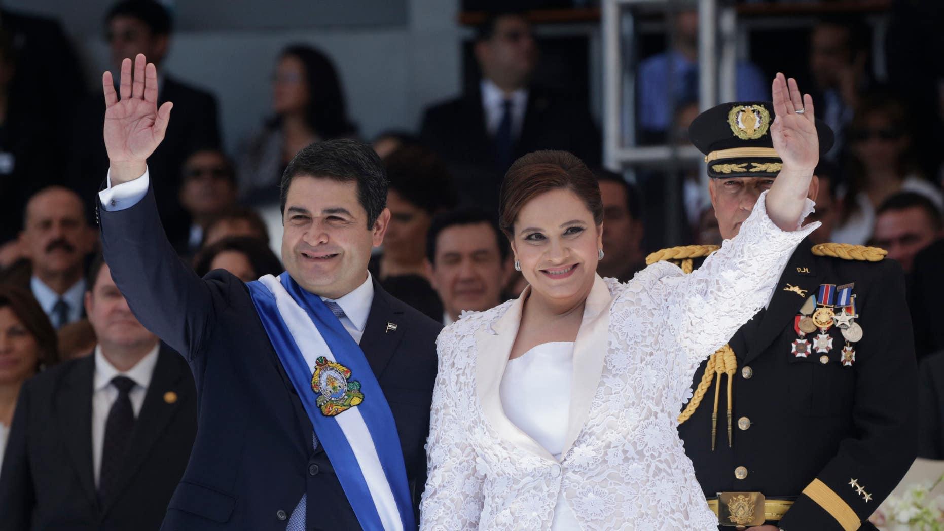 Honduras' President Juan Orlando Hernandez, left, and his wife Ana Rosalinda wave after his swearing in ceremony as new president in Tegucigalpa, Honduras, Monday, Jan. 27, 2014. (AP Photo/Arnulfo Franco)