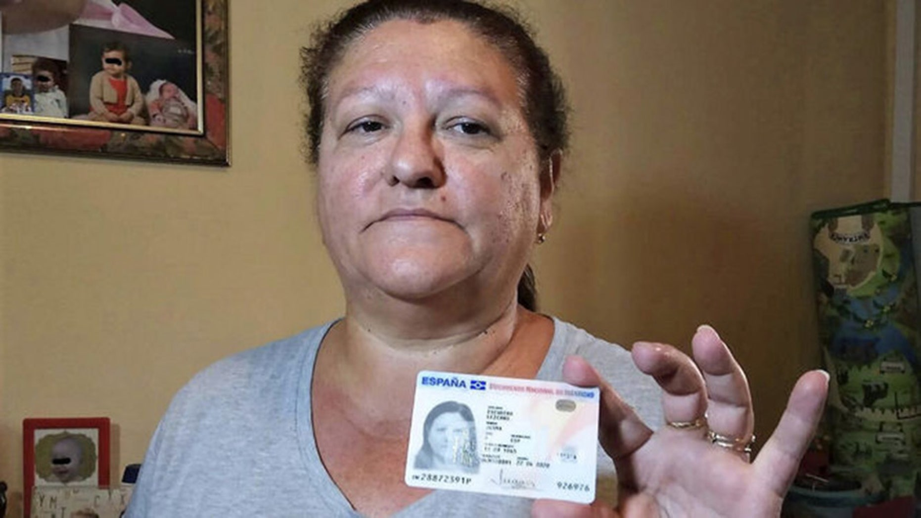 Juana Escudero, holding up her ID card, has a petition for a grave in Malaga, Spain be opened to prove that she is in fact alive.