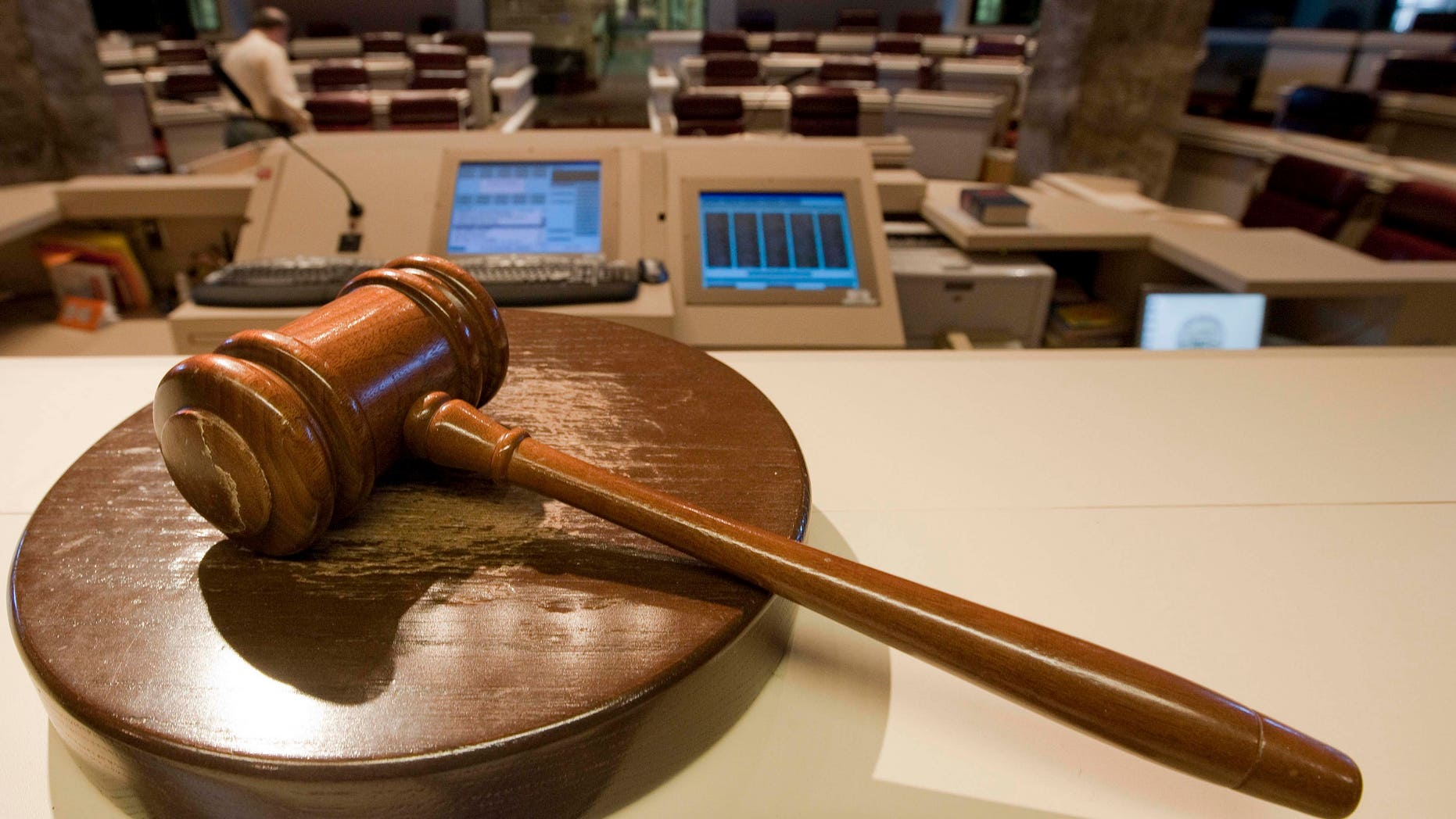 The gavel stands ready as Alabama House Public Information Officer Clay Redden, rear, makes preparations House chamber in Montgomery, Ala., on Friday, Dec. 3, 2010 a for the special session on ethics legislation called by Gov. Bob Riley.  The lawmakers come into session next Wednesday. (AP Photo/Dave Martin)