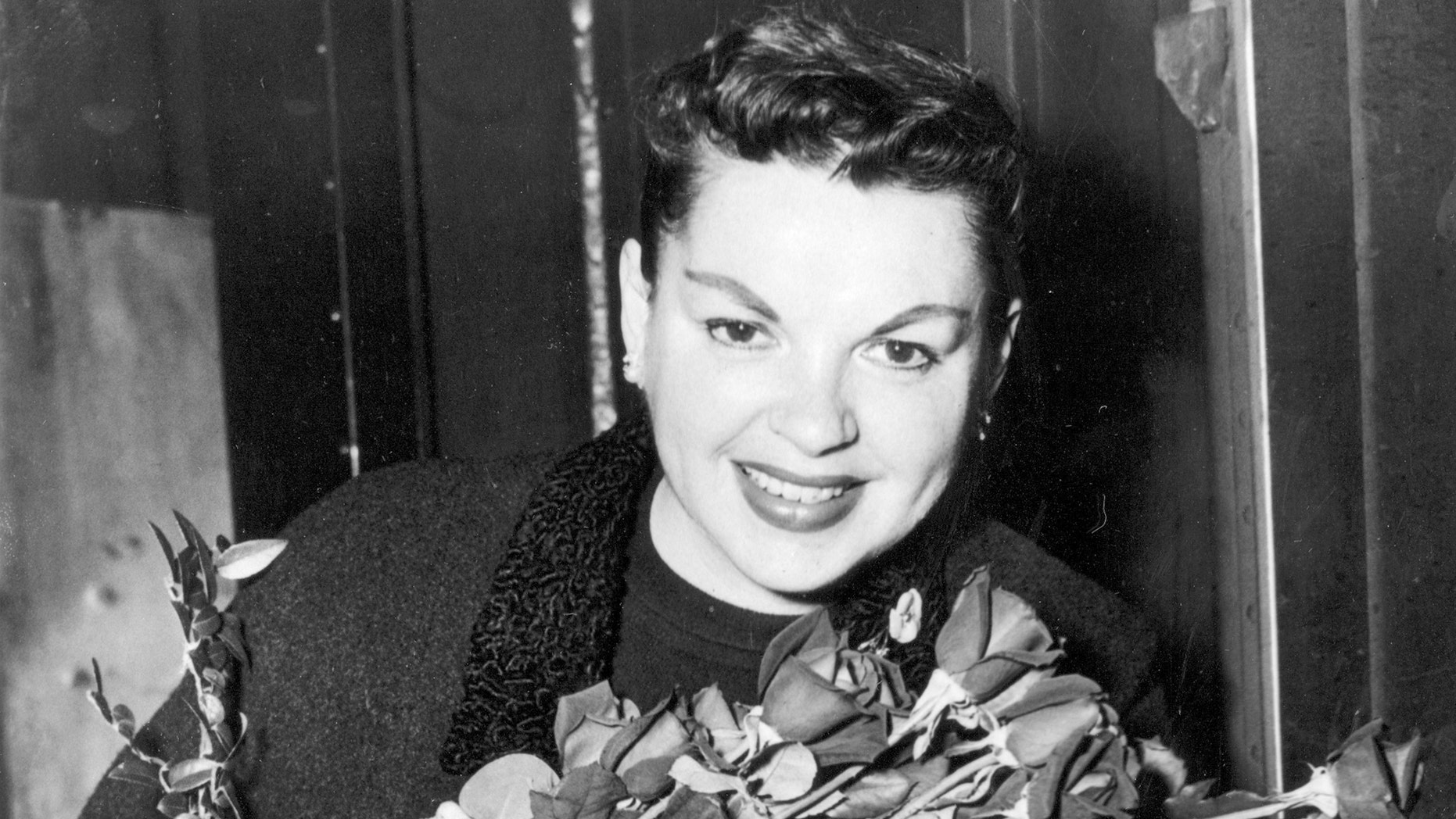 Judy Garland poses with long-stemmed roses in her arms as she arrives in New York City on Sept. 17, 1956.  The singer-actress is to begin rehearsals for her Sept. 26  Palace Theater engagement.  (AP Photo)