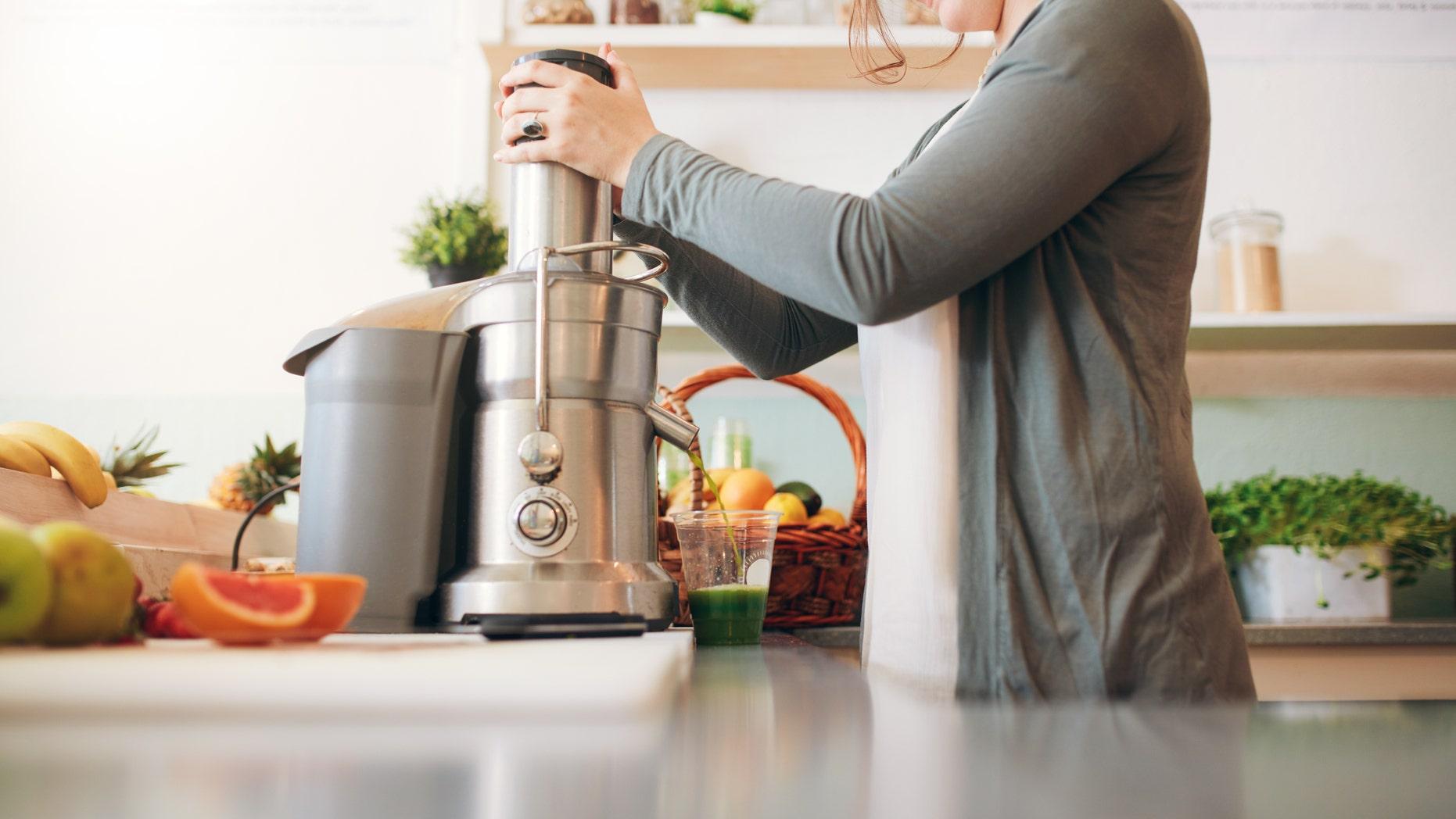 Cropped shot of  young female bar employee making fruit juice using juicer machine at counter.