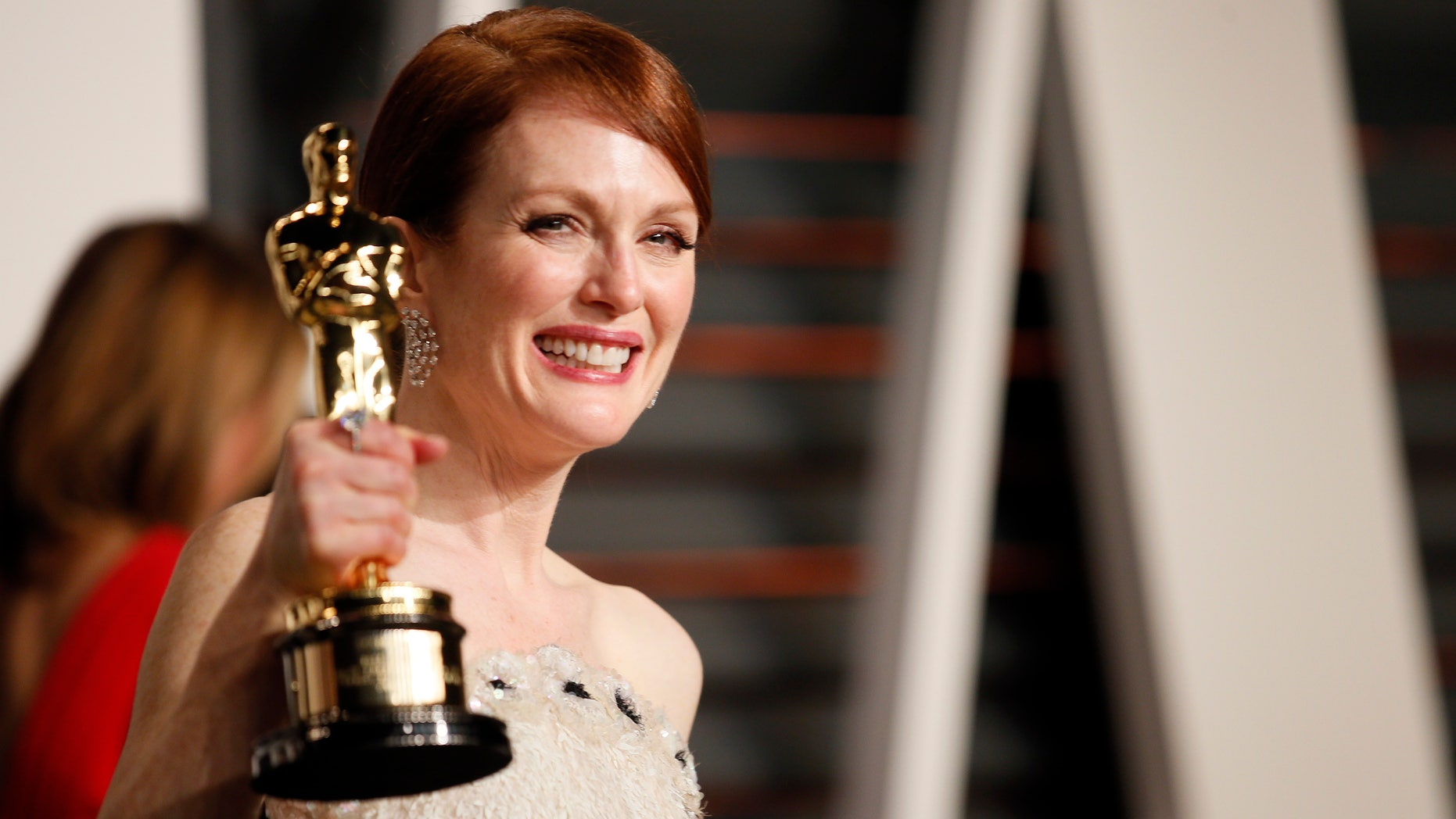 """Actress Julianne Moore with her Best Actress award for her role in the film """"Still Alice""""arrives at the 2015 Vanity Fair Oscar Party in Beverly Hills, California February 22, 2015. REUTERS/Danny Moloshok"""