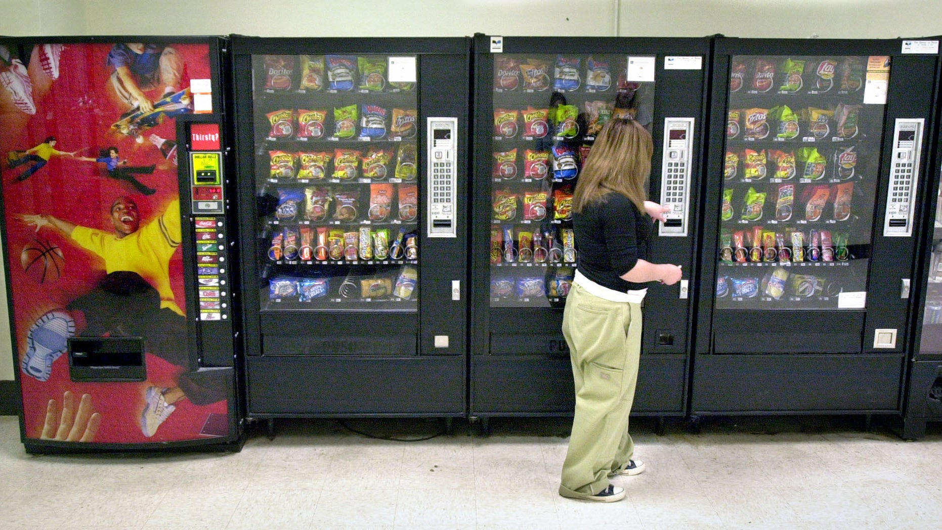 A student purchases a brown sugar Pop-Tart from a vending machine in the hallway outside the school cafeteria, in Wichita.
