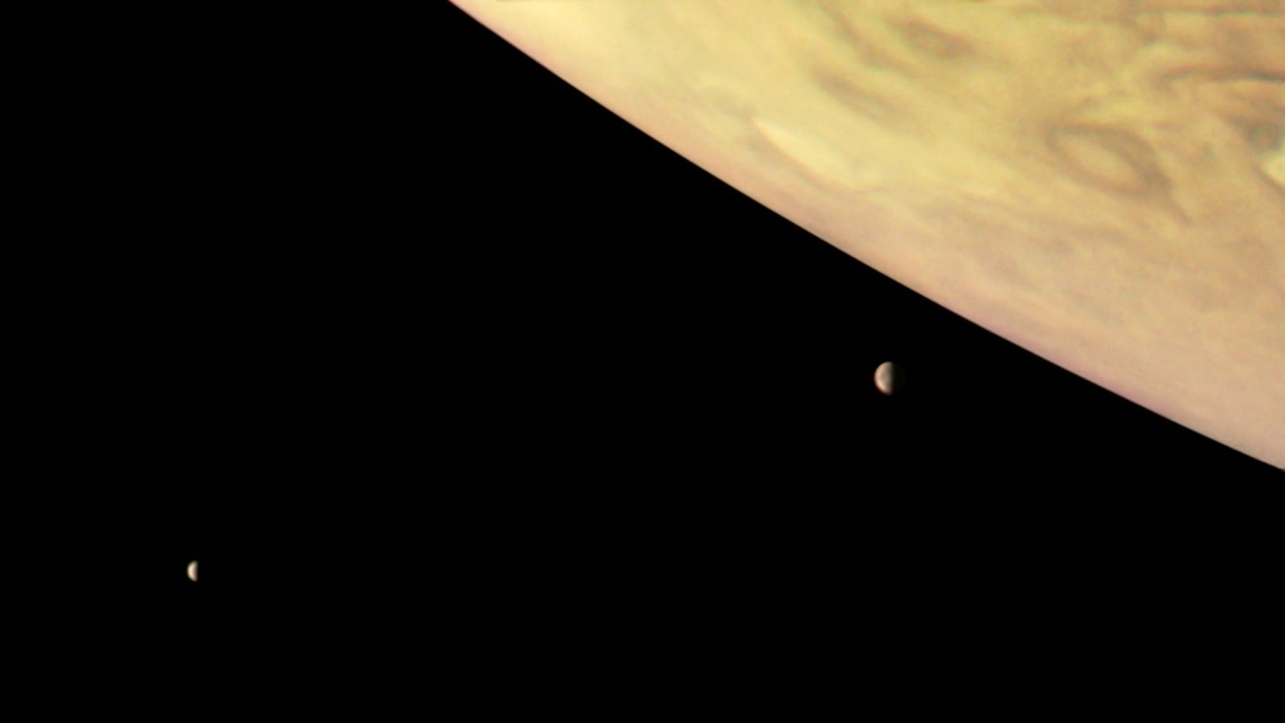 NASA's Juno spacecraft captured this image of Jupiter and two of its biggest moons, Io (right) and Europa (left), on Sept. 1, 2017. This color-enhanced version was processed by citizen scientist Roman Tkachenko using data from the probe's JunoCam imager.