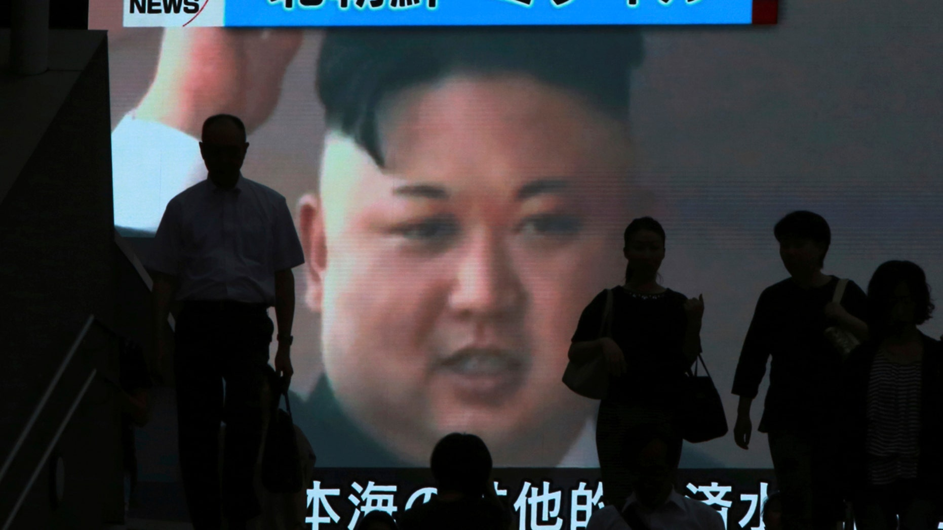 People in Tokyo walk past a TV news showing an image of North Korean leader Kim Jong Un.