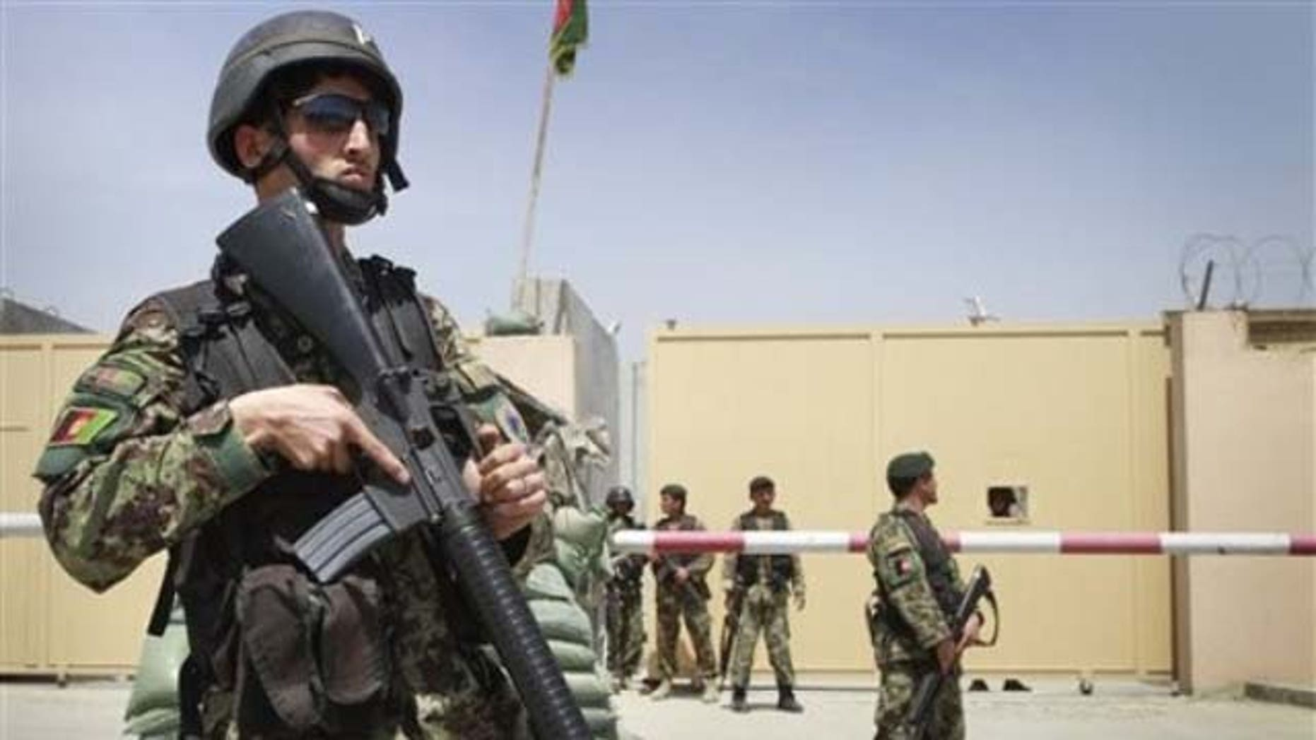 Afghan soldiers stand guard outside an airport gate in Kabul on April 27, 2011, after Col. Ahmed Gul killed 9 Americans.
