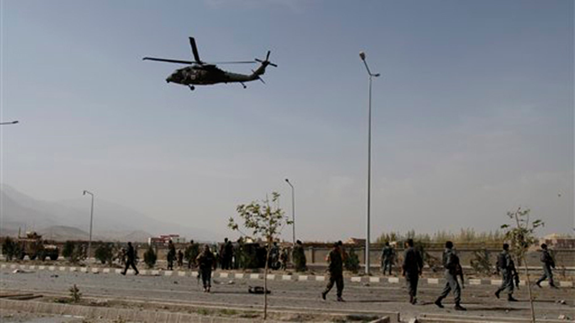 Oct. 29, 2011: A NATO helicopter flies above the site of a car bombing as Afghan security troops and U.S. soldiers gather at the site in Kabul, Afghanistan.