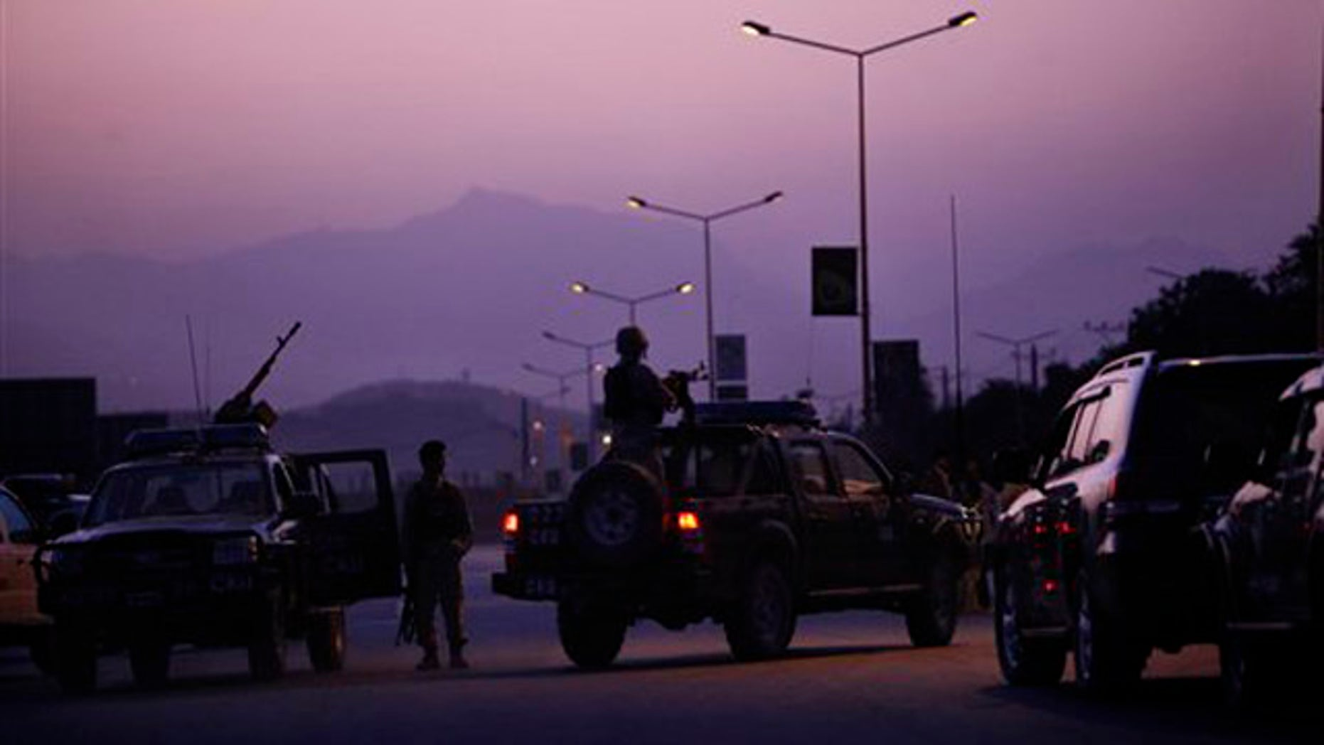 An Afghan army officer mans a heavy gun mounted to a vehicle at the entrance to the InterContinental hotel, which came under attack in Kabul, Afghanistan, June 29.