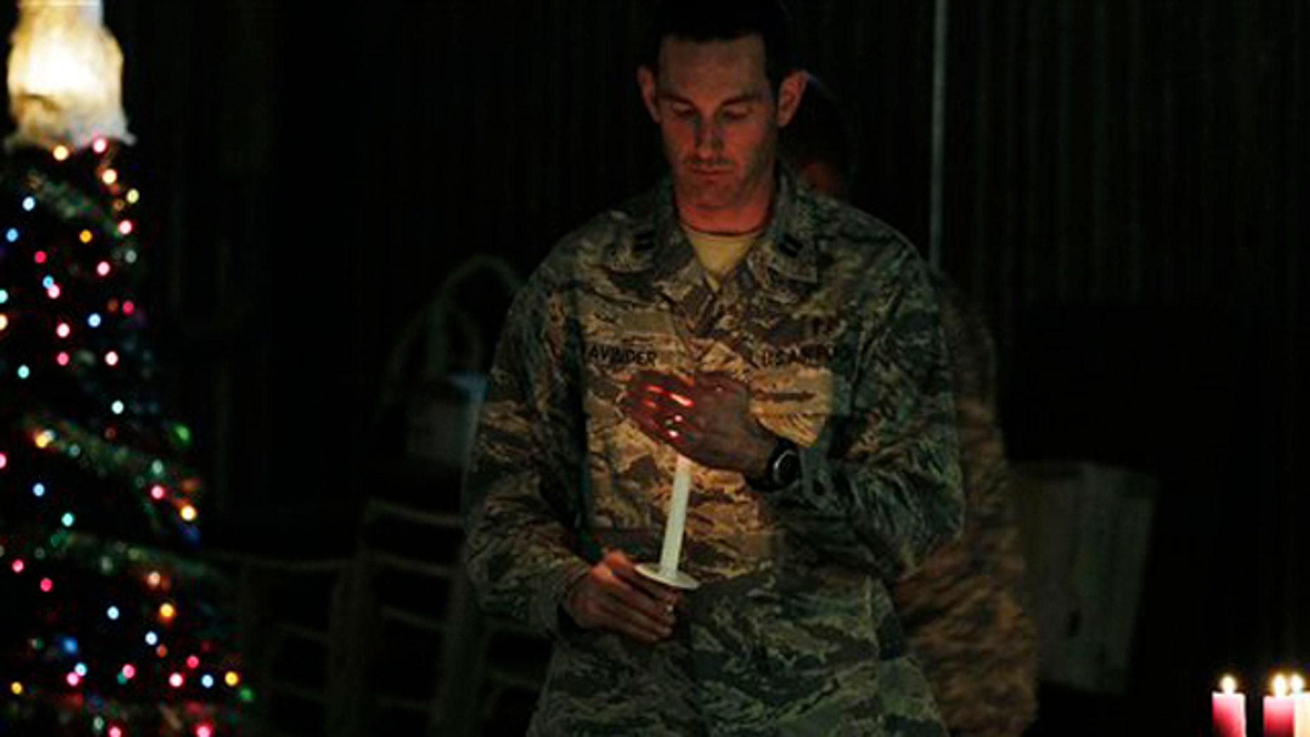 Dec. 24, 2010: A U.S. soldier carries a candle to light those of his colleagues during a ceremony on the eve of Christmas at the U.S. base of Camp Phoenix in Kabul, Afghanistan.