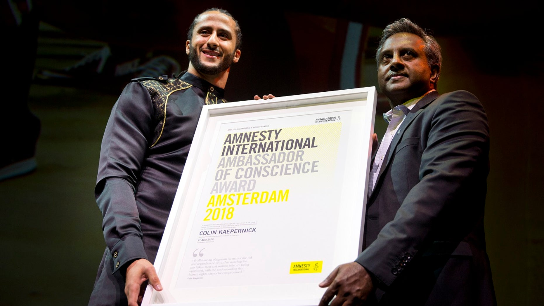 Former NFL quarterback and social justice activist Colin Kaepernick receives the Amnesty International Ambassador of Conscience Award for 2018 from Amnesty International Secretary General Salil Shetty, right, in Amsterdam, April 21, 2018.