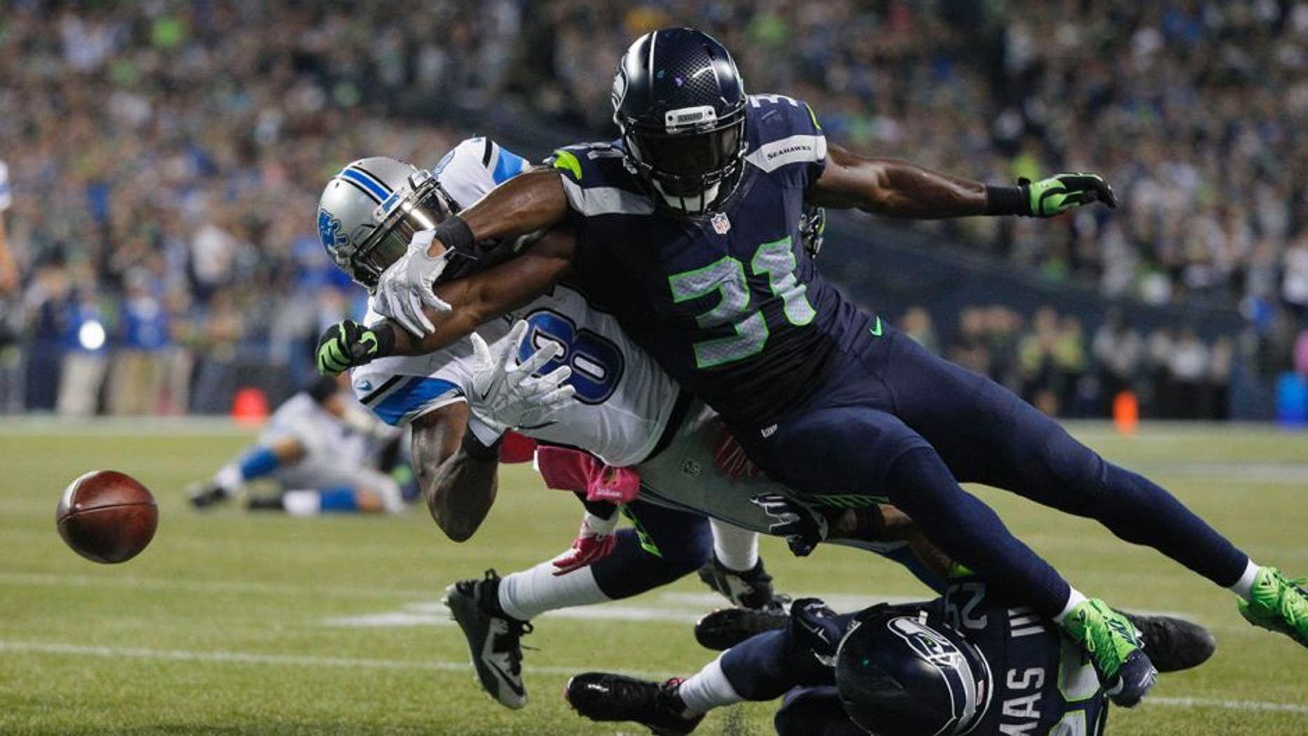 Oct 5, 2015; Seattle, WA, USA; Seattle Seahawks strong safety Kam Chancellor (31) forces a fumble by Detroit Lions wide receiver Calvin Johnson (81) during the fourth quarter at CenturyLink Field. Mandatory Credit: Joe Nicholson-USA TODAY Sports