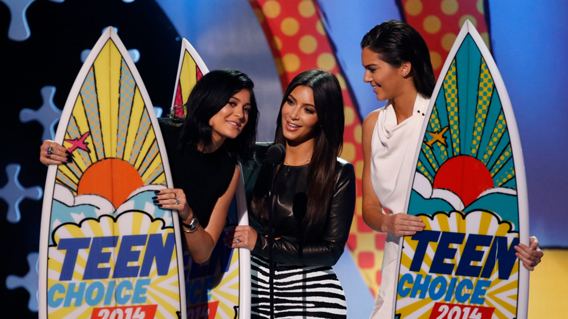 """Kylie Jenner, Kim Kardashian and Kendall Jenner accept the choice reality show award for """"Keeping Up with the Kardashians"""" during the Teen Choice Awards 2014 in Los Angeles, California August 10, 2014."""