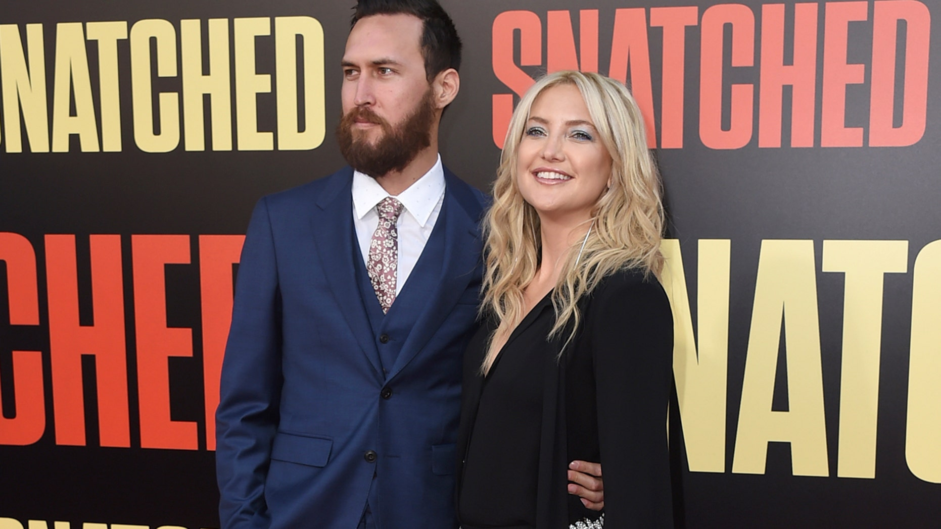 "Danny Fujikawa, left, and Kate Hudson arrive at the Los Angeles premiere of ""Snatched"" at the Regency Village Theatre on Wednesday, May 10, 2017. (Photo by Jordan Strauss/Invision/AP)"
