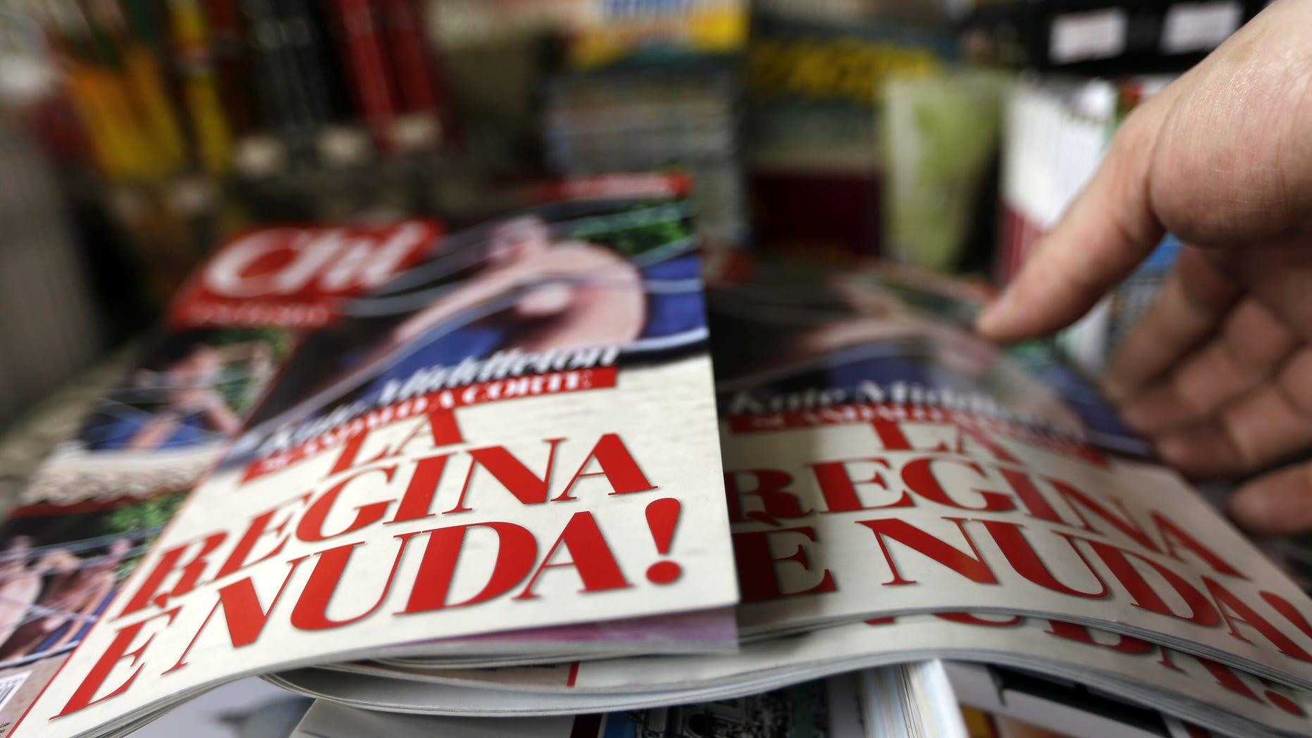 """A newstands owner adjusts copies of the Italian magazine Chi reading in Italian """"The queen is naked"""" in Rome, Monday, Sept. 17, 2012. An Italian gossip magazine owned by former Premier Silvio Berlusconi published a 26-page spread of topless photos of Britain's Prince William's wife Kate on Monday despite legal action in France against the French magazine that published them first. Chi hit newsstands on Monday, featuring a montage of photos taken while the Duke and Duchess of Cambridge were on vacation at a relative's home in the south of France last month. They included the 14 pictures published by the popular French magazine Closer, which like Chi is owned by Berlusconi's Mondadori publishing house. (AP Photo/Alessandra Tarantino)"""