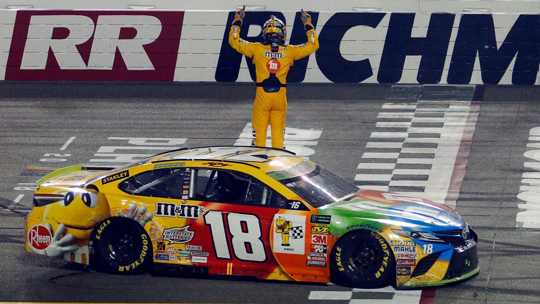 Kyle Busch (18) celebrates winning the NASCAR Cup Series auto race at Richmond Raceway in Richmond, Va., Saturday, Sept. 22, 2018. (AP Photo/Steve Helber)