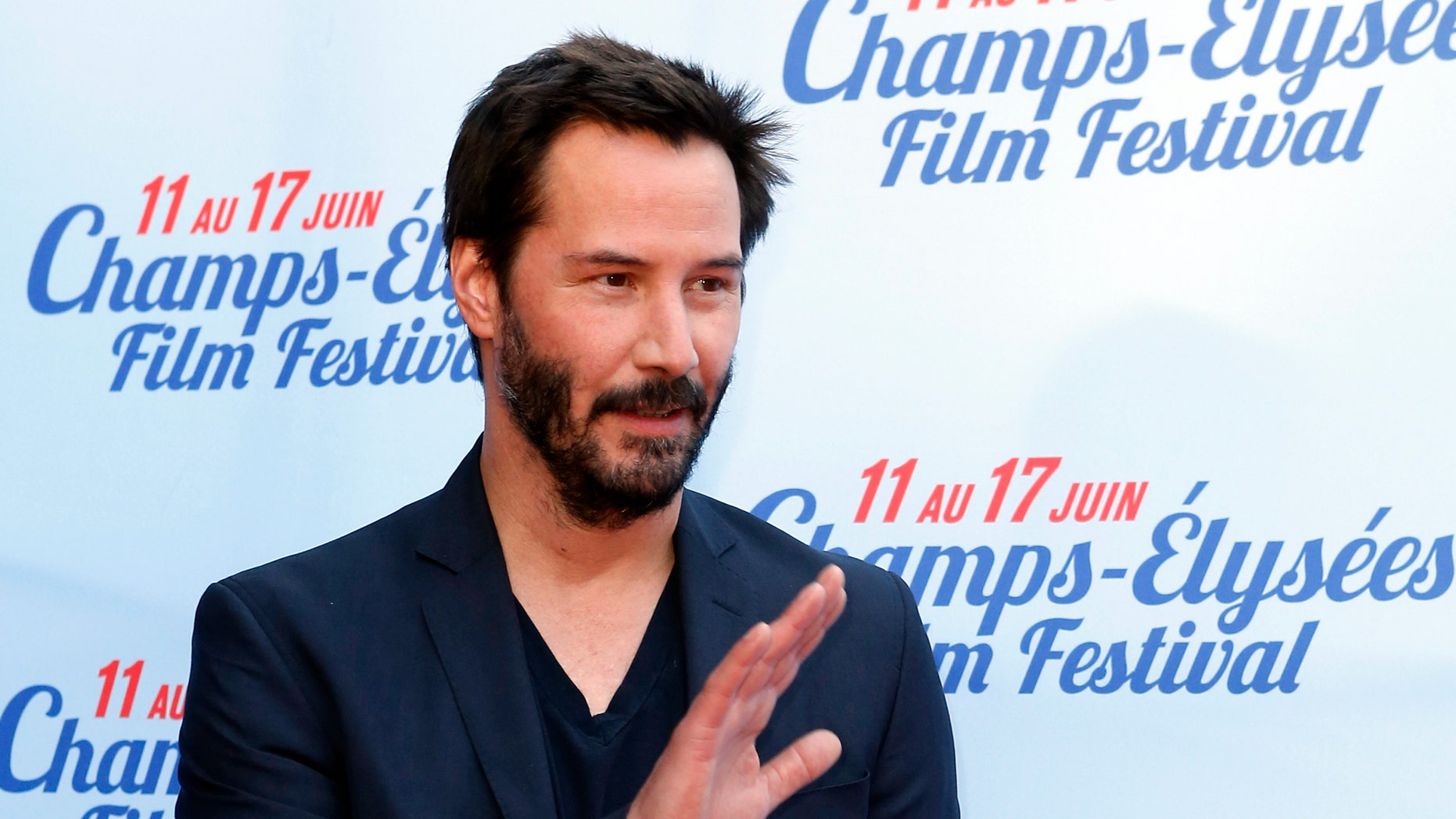 """June 14, 2014. Keanu Reeves waves at the screening of the film """"Side by Side"""" during the Champs-Elysees Film Festival, in Paris."""
