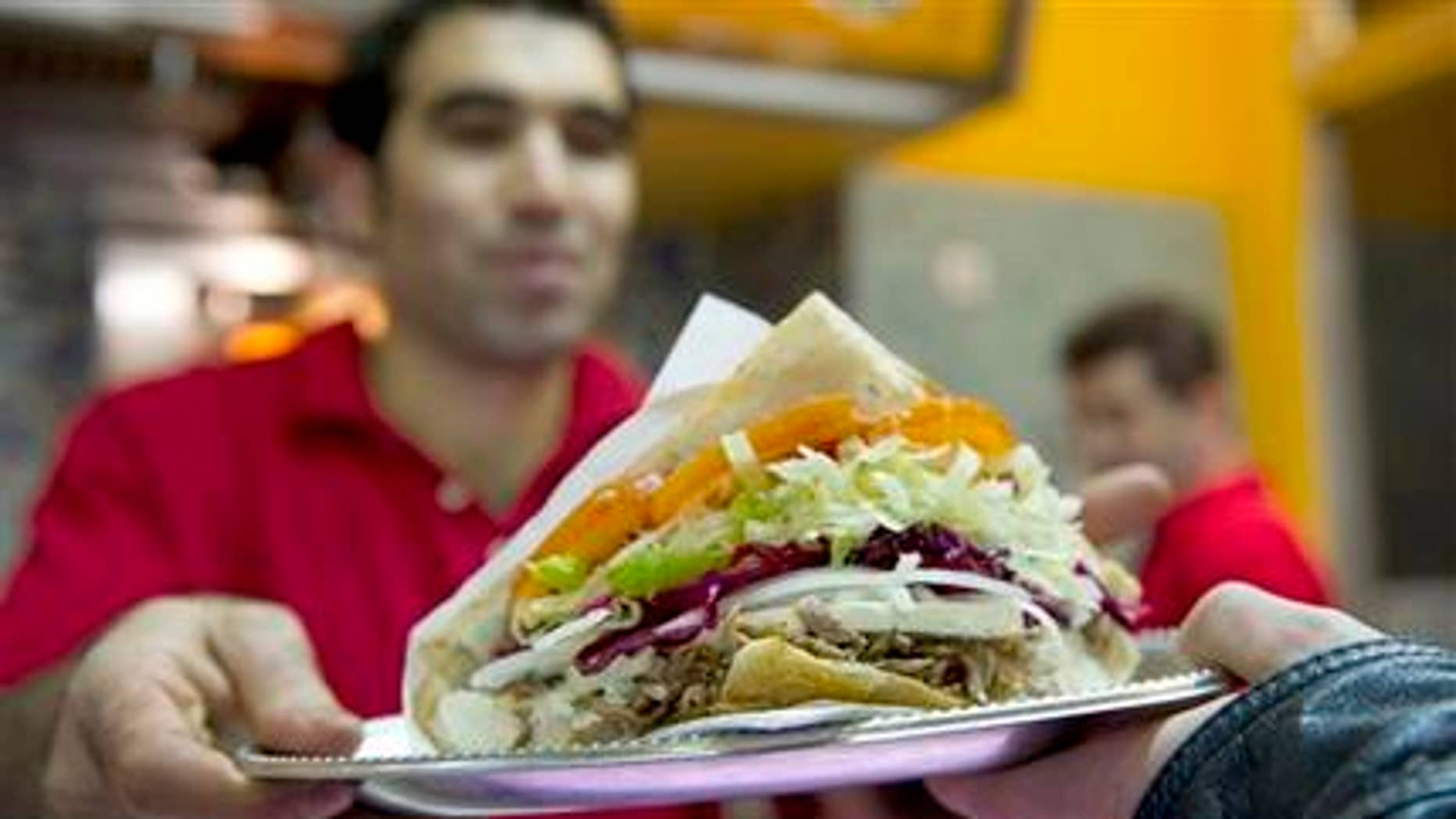 Turkish Abdullah Ekinci serves a doner kebab in a Turkish restaurant in Berlin, Germany, Sunday, March 21, 2010. Forget about bratwurst, currywurst and other kinds of sausages _ doner kebab, or shawarma, has overtaken traditional German fast food as the country's favorite snack on the go.     (AP Photo/Gero Breloer)