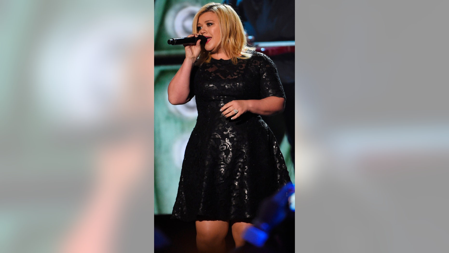 """Kelly Clarkson performs """"How Blue"""" as a tribute to Reba McEntire, the recipient of the first NASH Icon Award, during the American Country Countdown Awards in Nashville, Tennessee December 15, 2014."""