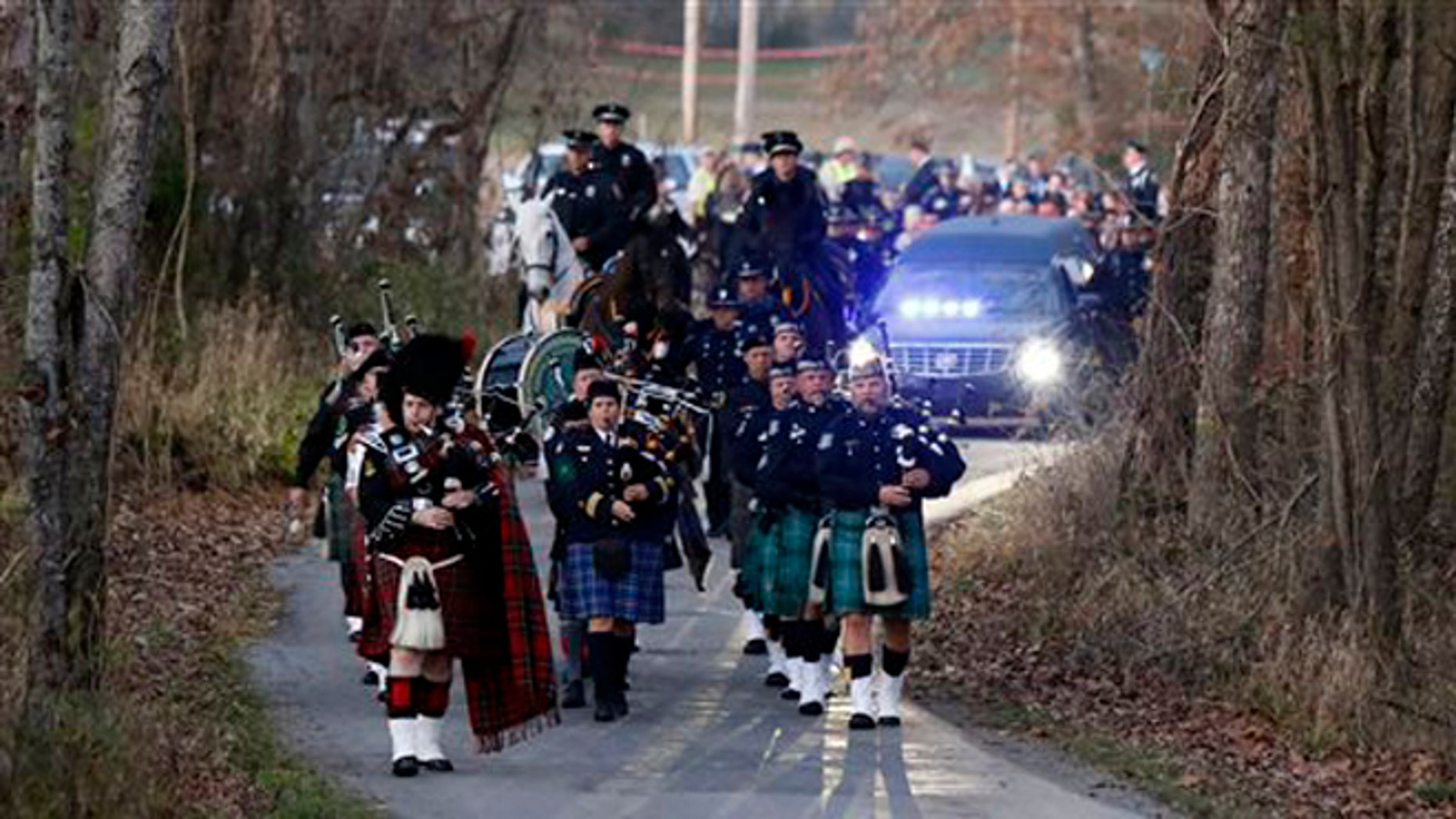 Nov. 11, 2015: Pipers and members of the Lexington Mounted Police lead the hearse during the funeral procession for Richmond Police Officer Daniel Ellis near Dunnville, Ky.