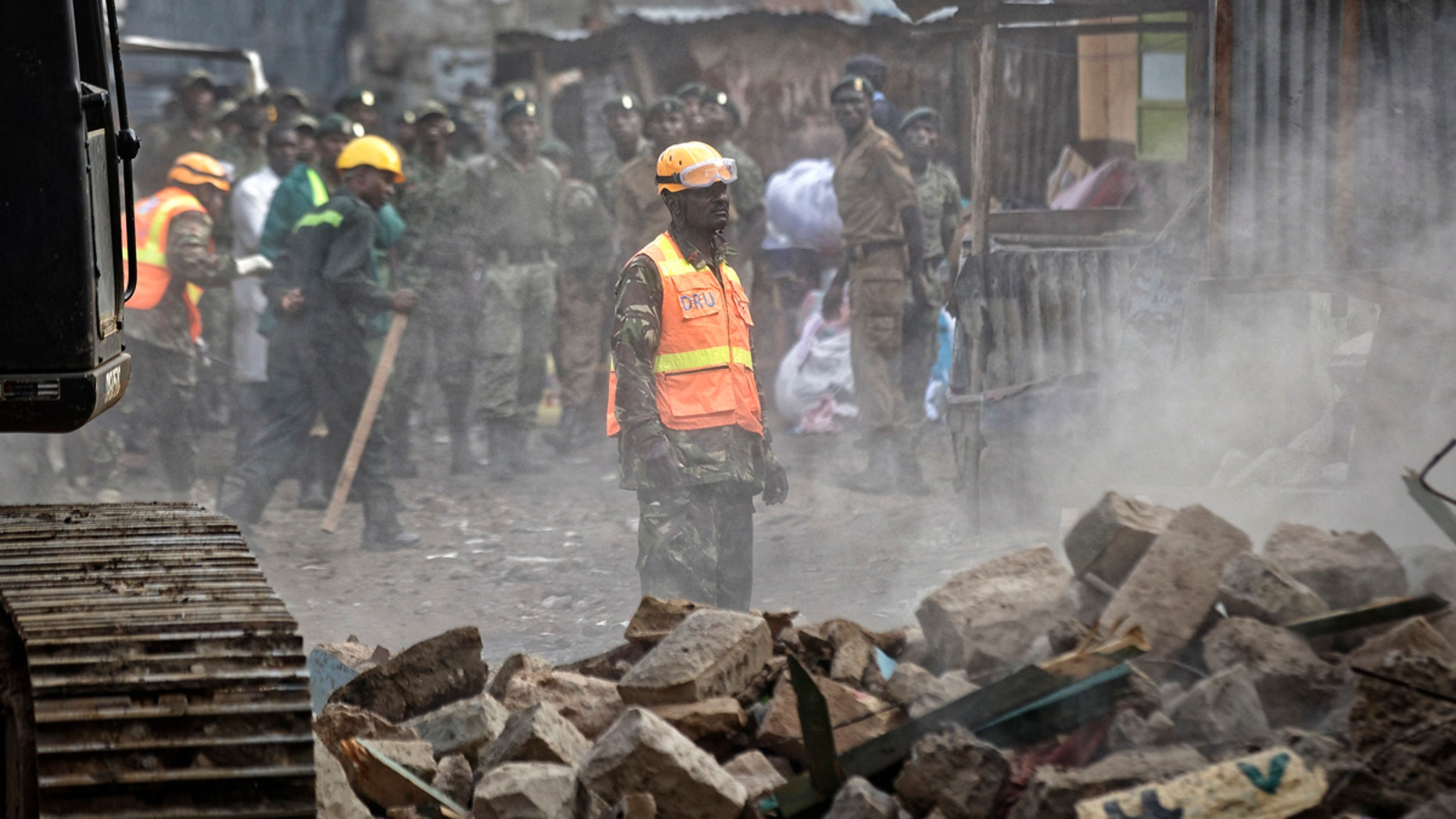 A rescuer aided by a heavy digger attends the scene of a five-storey collapsed building in the Huruma neighborhood of Nairobi, Kenya, June 3, 2018.
