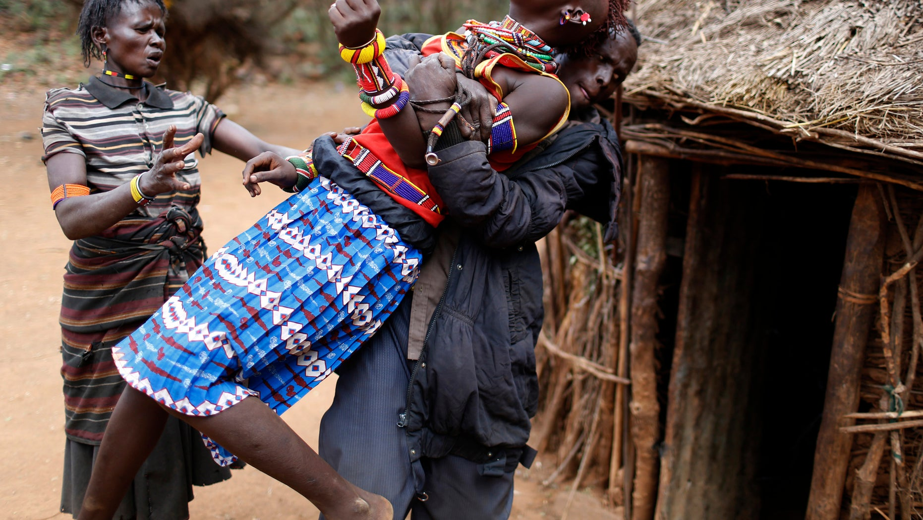 A man holds a girl as she tries to escape when she realised she is to to be married, about 80 km (50 miles) from the town of Marigat in Baringo County December 7, 2014. REUTERS/Siegfried Modola