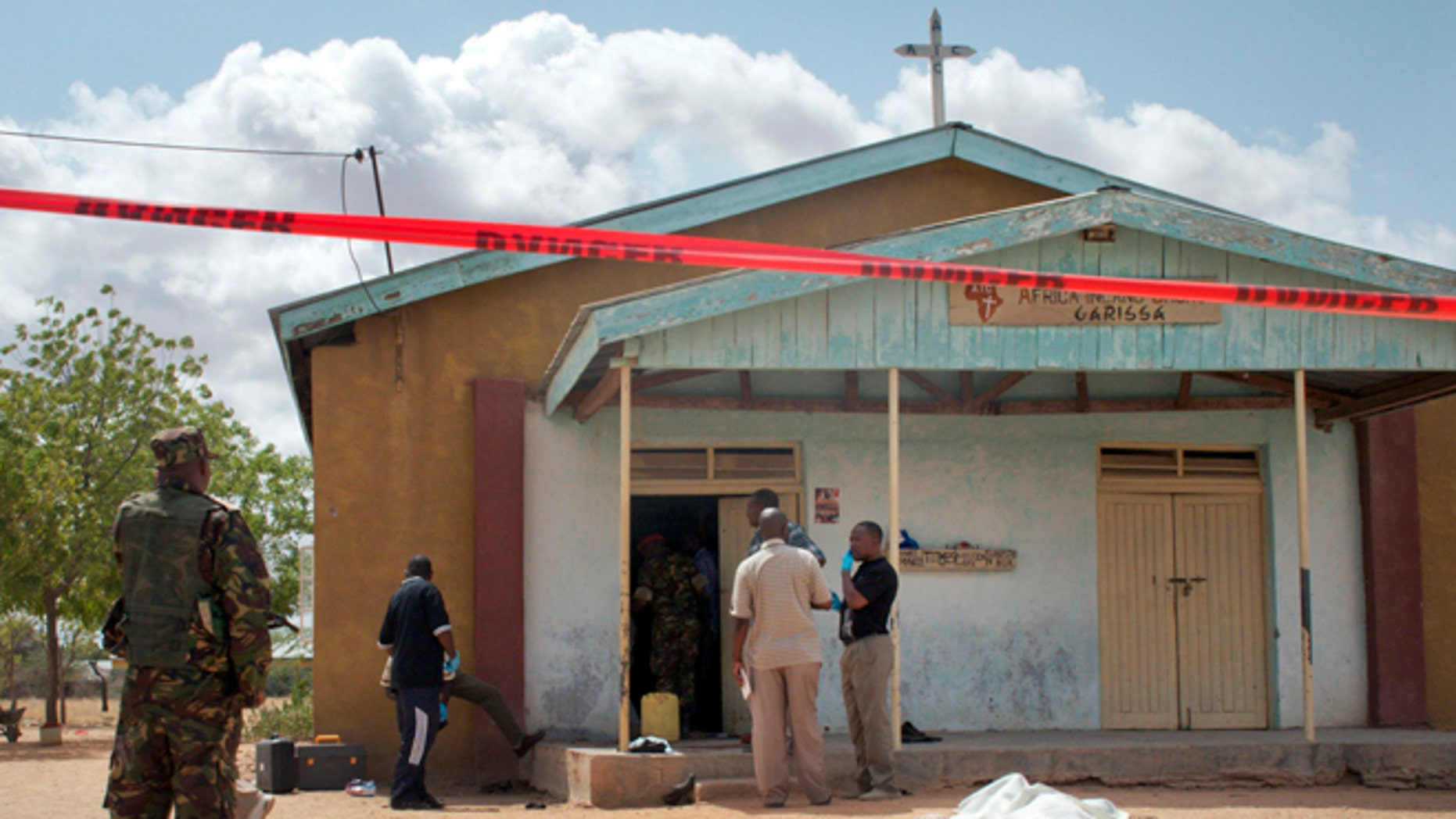 July 1, 2012: Members of the Kenyan security forces inspect the scene, as a body lies covered by a sheet, outside the African Inland Church in Garissa, Kenya.