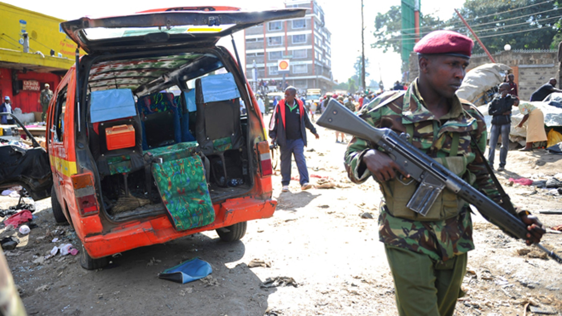 May 16, 2014: A member of the security forces patrols at the site where two blasts detonated, one in a mini-van used for public transportation, in a market area of Nairobi, Kenya.
