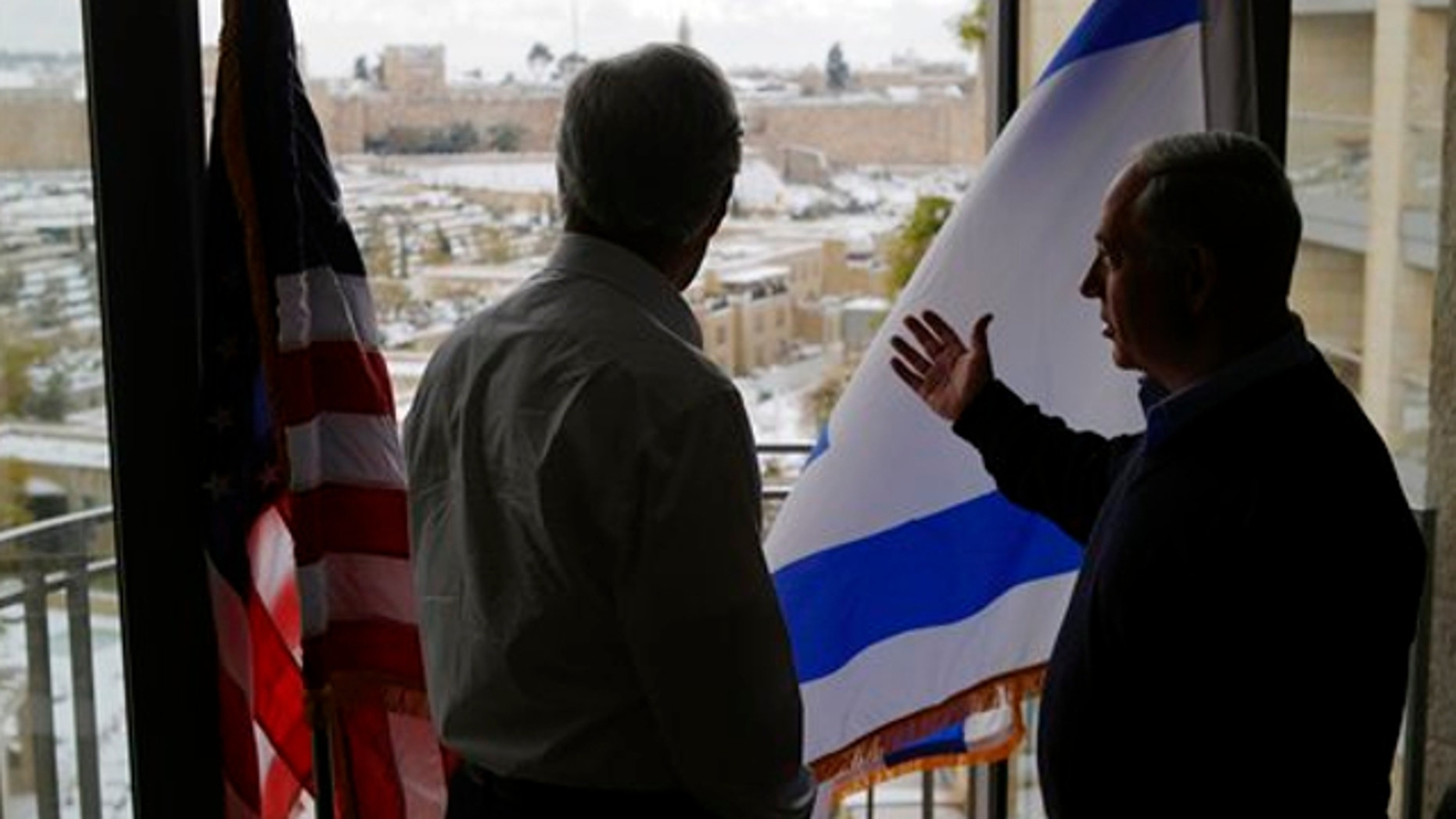 Dec. 12, 2013: Secretary of State John Kerry, left, and Israeli Prime Minister Benjamin Netanyahu look out onto the snow-covered city of Jersusalem during a meeting in Jerusalem.