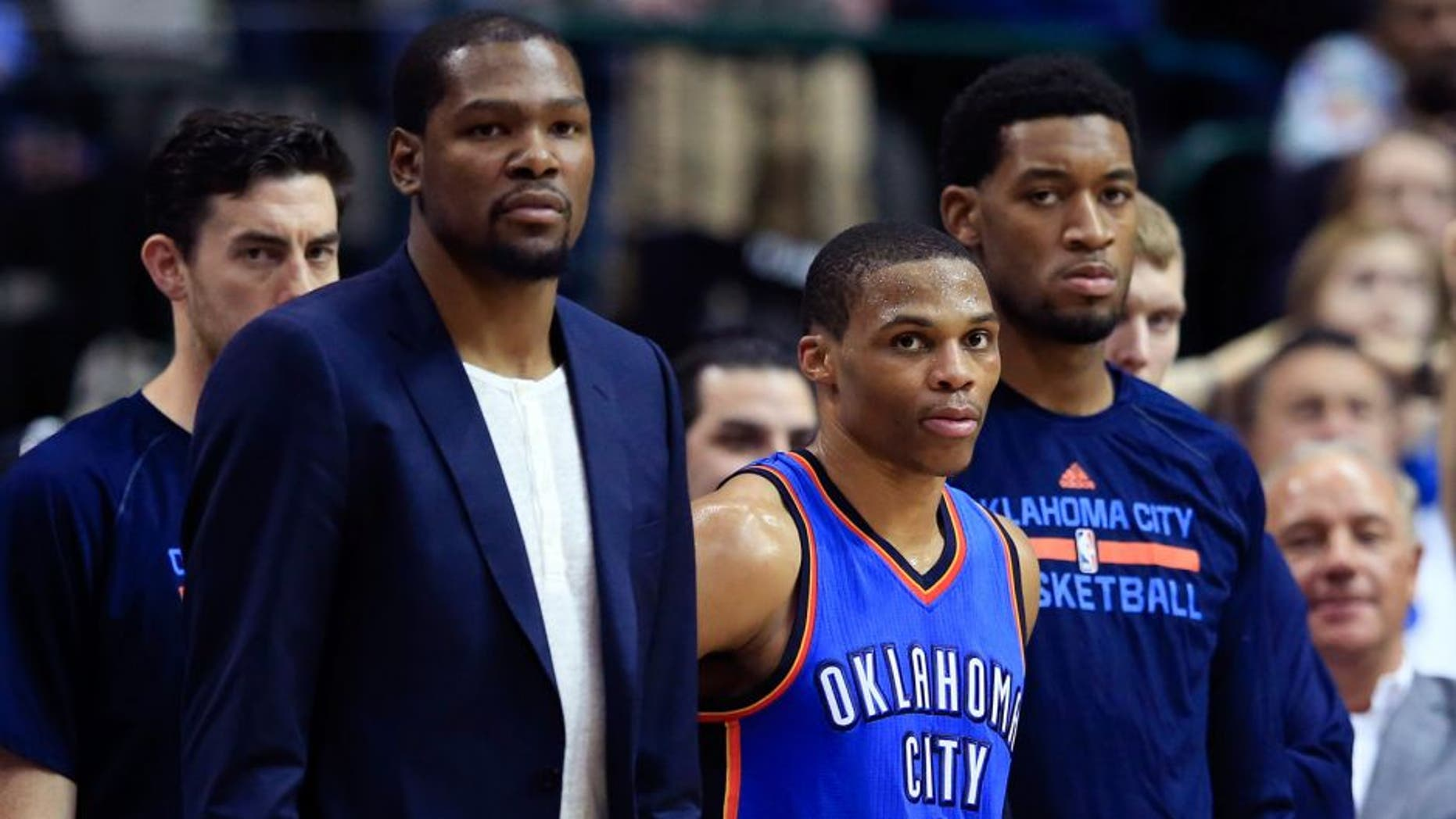 Mar 16, 2015; Dallas, TX, USA; Oklahoma City Thunder forward Kevin Durant (left) and guard Russell Westbrook (0) and forward Perry Jones (right) react on the bench during the second half against the Dallas Mavericks at American Airlines Center. Mandatory Credit: Kevin Jairaj-USA TODAY Sports