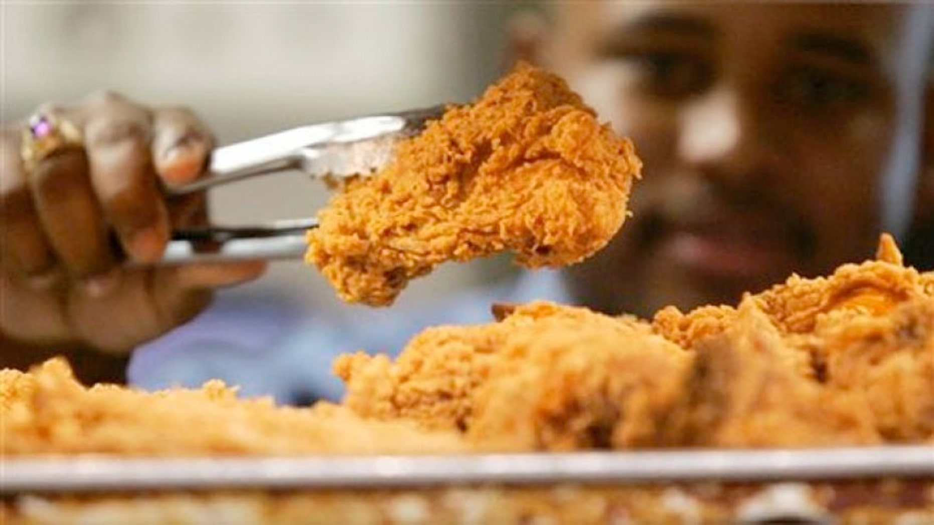 FILE: A Kentucky Fried Chicken employee uses tongs to hold up an sample of the company's trans fat-free Extra Crispy fried chicken in New York.