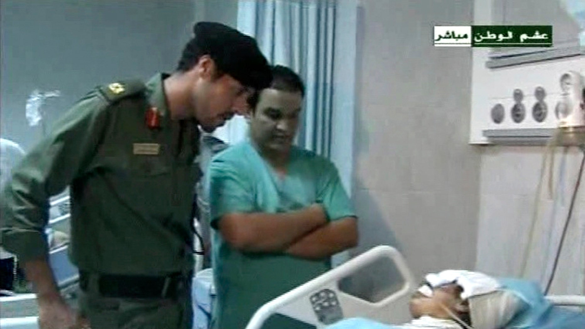 Aug. 10: This video image broadcast Wednesday by Libyan TV purports to shows Muammar al-Qaddafi's youngest son Khamis Qaddafi, left, who commands one of the best trained and equipped units in the Libyan military, visiting an injured man in a hospital in Tripoli, Libya on Tuesday Aug. 9.