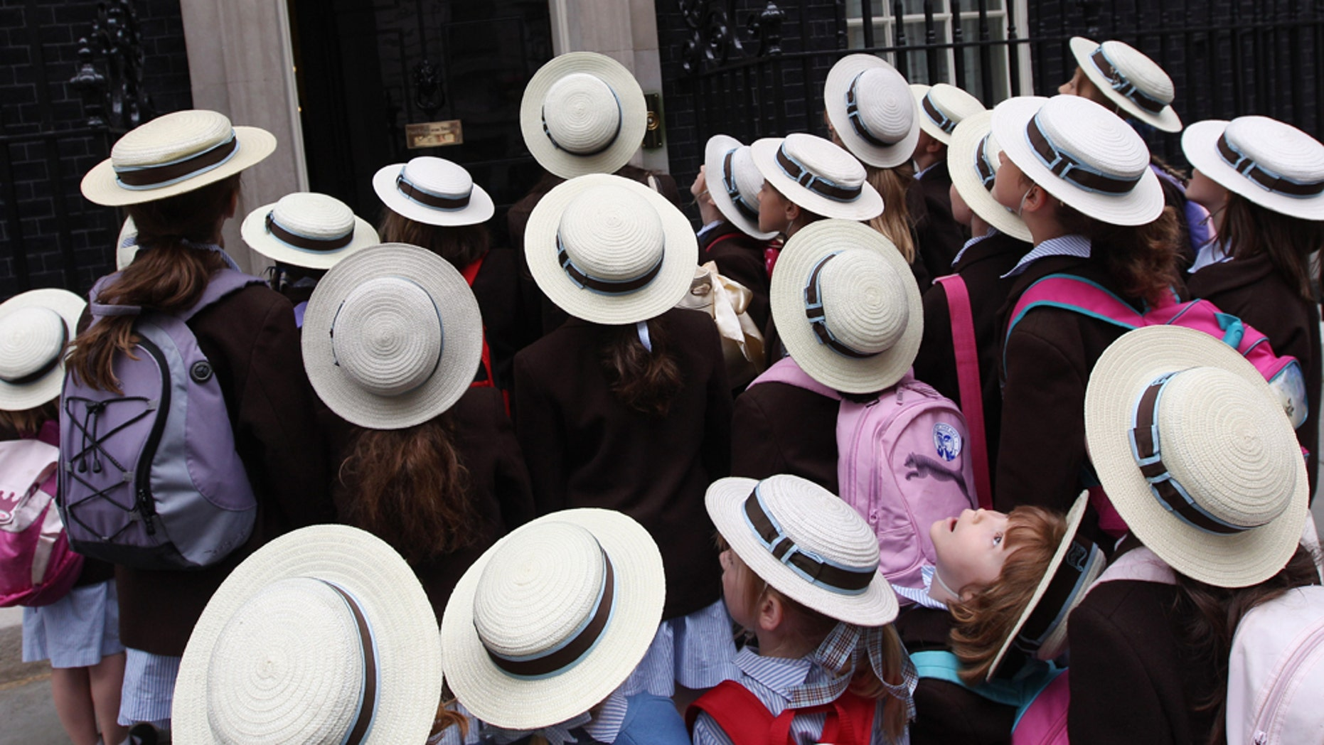 LONDON, ENGLAND - JULY 13:  Schoolchildren from St Hilda's Junior School stand outside the entrance to Number 10 while visiting Downing Street on July 13, 2010 in London, England.  (Photo by Dan Kitwood/Getty Images)