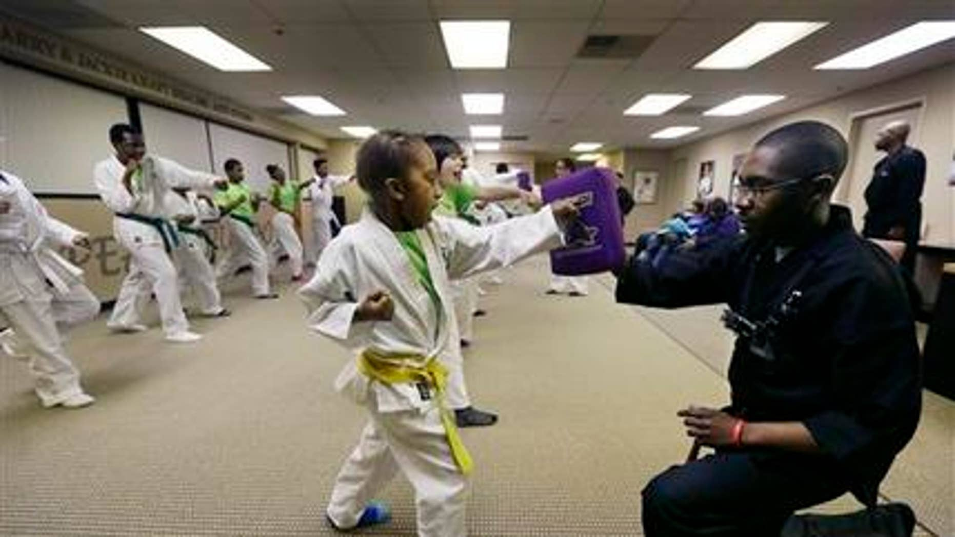 Jan. 28, 2015: In a photo in Southfield, Mich. Jayson Harris punches a pad held by Michael Hunt during the Kids Kicking Cancer class.