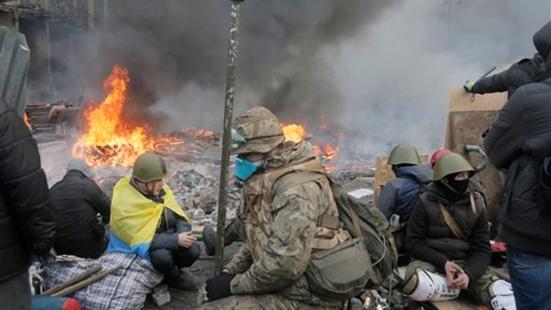 Anti-government protesters relax at the barricades during clashes with riot police in Kiev's Independence Square, the epicenter of the country's current unrest, Kiev, Ukraine, Wednesday, Feb. 19, 2014.  The deadly clashes in Ukraines capital have drawn sharp reactions from Washington, generated talk of possible European Union sanctions and led to a Kremlin statement blaming Europe and the West. A roundup of some of the international reactions. (AP Photo/Efrem Lukatsky)