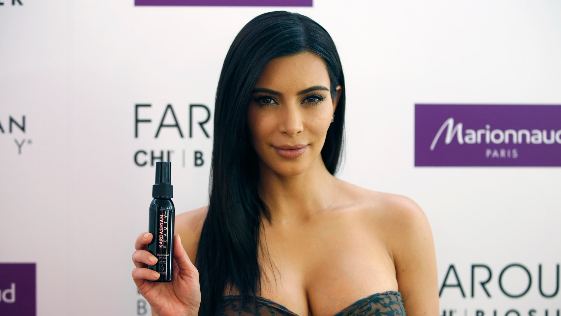 April 15, 2015. TV star Kim Kardashian poses as she presents her Kardashian Beauty Hair collection for Marionnaud at the flagship store on the Champs-Elysees in Paris.