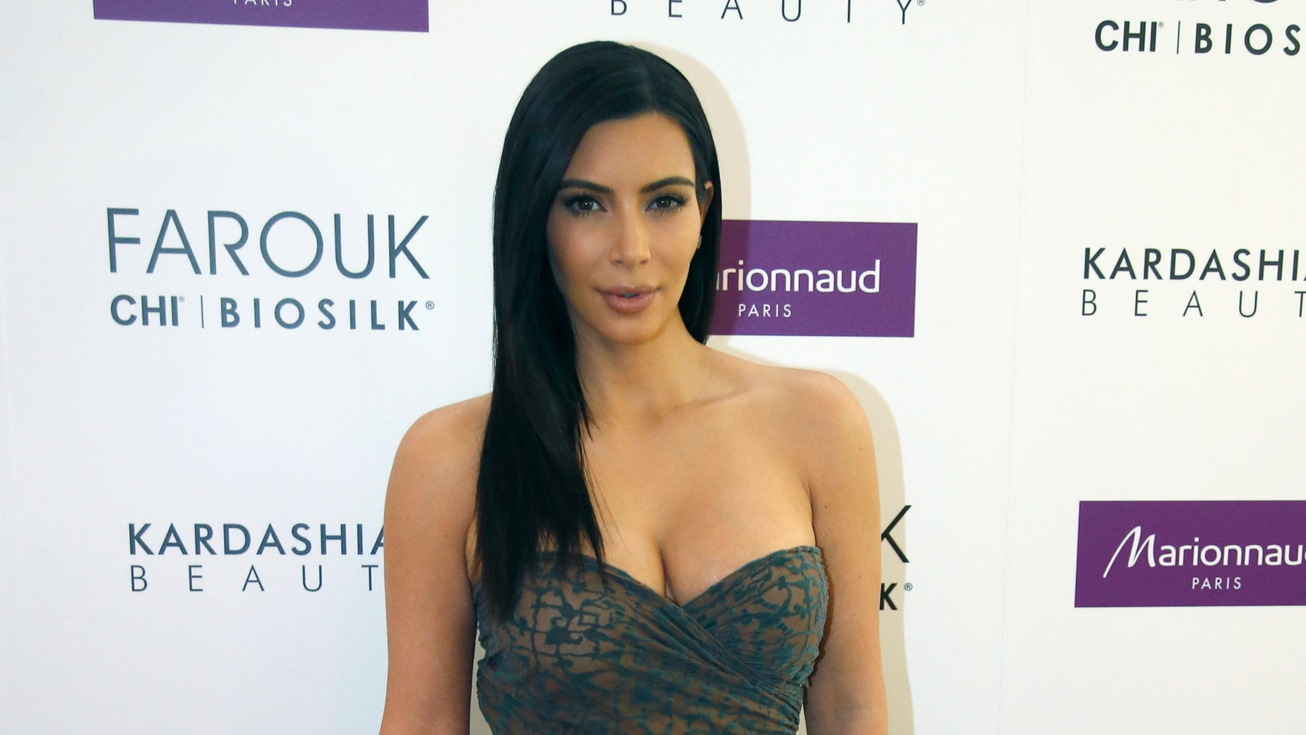 April 15, 2015. Kim Kardashian poses as she presents her Kardashian Beauty Hair collection for Marionnaud at the flagship store on the Champs-Elysees in Paris.