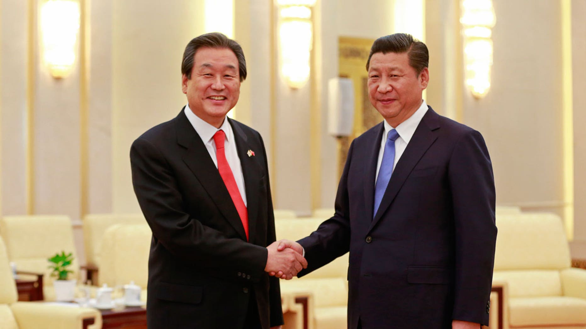 South Korean politician Kim Moo-sung (L) is seen greeting Chinese President Xi Jinging in 2014.