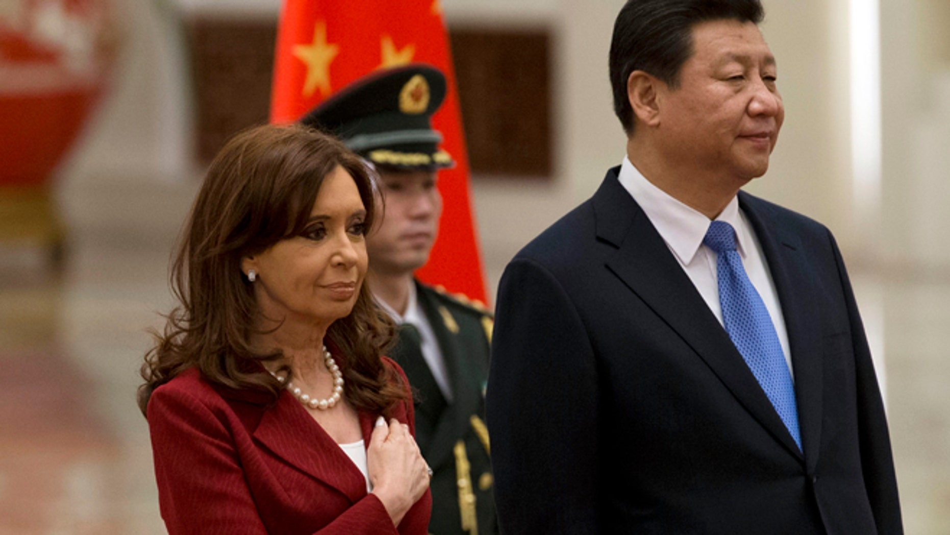 Argentine President Cristina Fernandez places her hand over her chest as she stands next to Chinese President Xi Jinping while the Argentine national anthem is played during a welcome ceremony at the Great Hall of the People in Beijing Wednesday, Feb. 4, 2015. (AP Photo/Ng Han Guan)