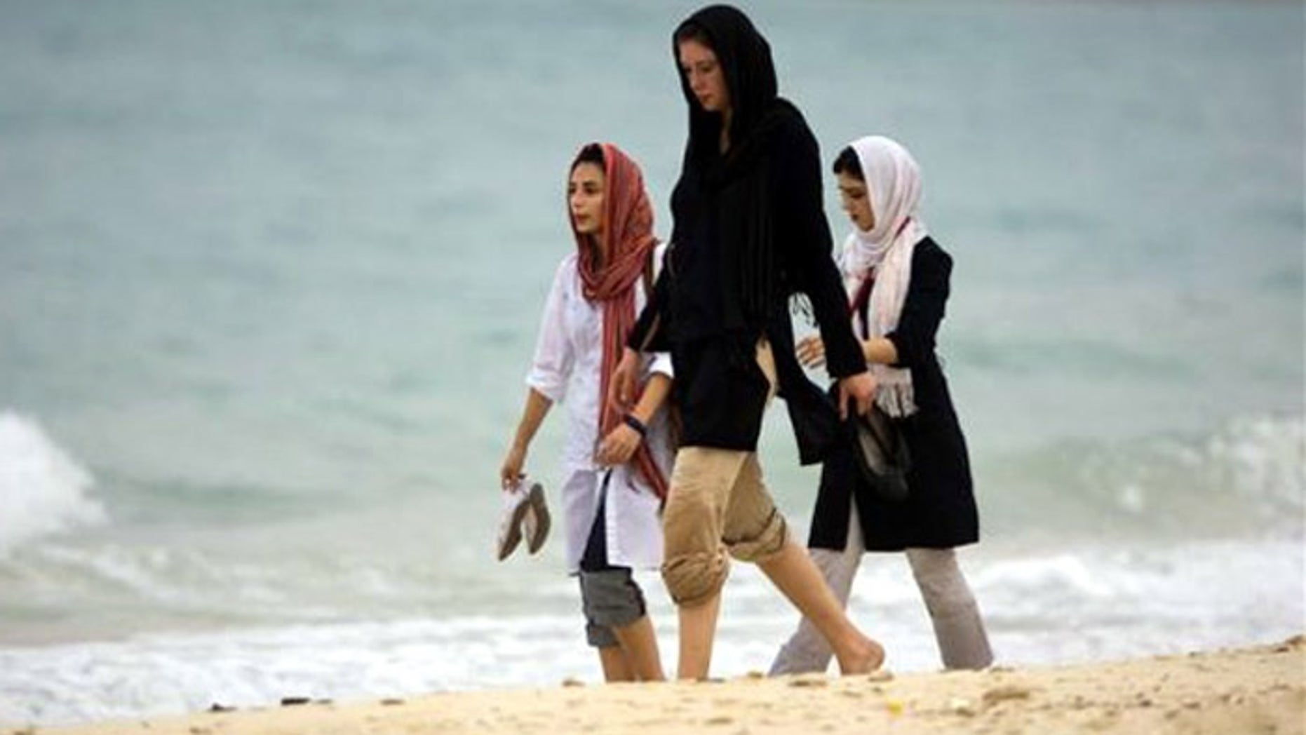 Iranian women walk along the southern beach on the island of Kish in the Persian Gulf, south of Tehran. (Reuters)